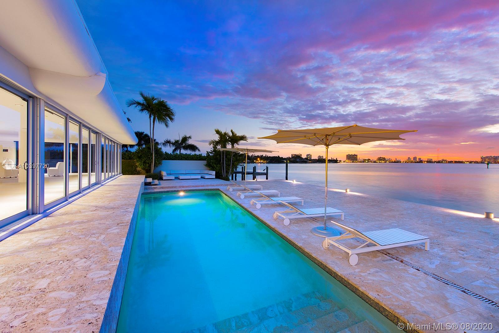 Best views on the island! Located at the tip of guard gated Biscayne Point in Miami Beach, you'll marvel at the panoramic open bay and downtown views. Watch sunsets from the expansive sliding glass doors of this stunning MiMo waterfront home. A large 12,000 sq. ft. lot with 100 feet of waterfront and over 1,100 sq. ft. of tiled dock offers a backyard oasis with pool, spa and cabana bath. Luxurious open floor plan has book-matched Calcatta marble and limestone. Professional kitchen boasts Boffi cabinets, Nero Portoro marble and appliances from Miele, Subzero, and Gaggenau. Master suite includes custom walk-in Ornare closet, marble bath and steam shower. The property has Savant home automation, security cams, backup generator, and is surrounded by a gated 6 ft. wall for the utmost privacy.