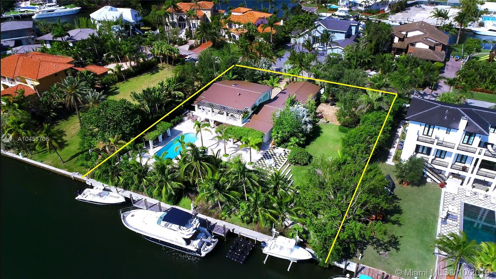 Nestled on a Double Lot - this home features 4 beds / 5.1 baths on a 27,900 sf gated lot in Coral Gables guard/gated community, Sunrise Harbour. The property boasts 160 ft water frontage, on a wide channel and includes a private dock and boat lift with direct ocean access. Master suite is located on the second floor with 2 separate bathrooms, oversized walk-in closet, sitting area and private terrace overlooking the manicured European-style backyard. Open kitchen with Subzero refrigerator and Viking appliances. Large formal dining area with wood beam ceiling opens to an alluring lush pergola covered terrace, summer kitchen and pool. Family room includes stone fireplace. 2 driveways and air conditioned 3 car garage with workshop area and service quarters with full bath.