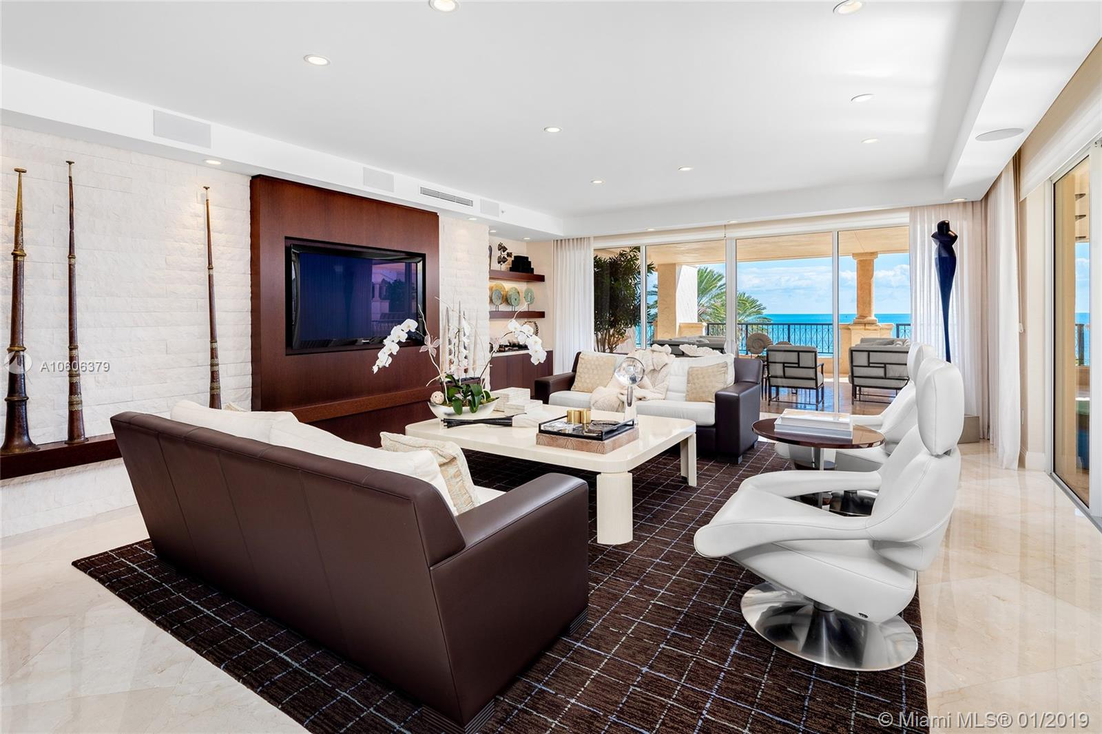 This 3BR/3+1BA Oceanside corner unit features 3,691 SF of immaculately designed interior spaces w/Crema Marfil marble floors, Venetian plaster walls & large ocean side wraparound terrace w/unobstructed sunrise beach & Atlantic Ocean views. Spacious open living room w/a beautiful onyx bar & dining room surrounded by walls of glass that stream natural lighting. An amazing gourmet kitchen sports top of the line Miele & Sub-Zero appliances, custom Snaidero cabinetry & a large breakfast area. The sumptuous master suite offers an office space, direct terrace access & stunning master bath w/limestone floors, walk-in rain shower & sunken spa tub. The other two bedrooms each with en-suite bathrooms & share a terrace w/Fisher Island views.  5-star Fisher amenities complete this offering.