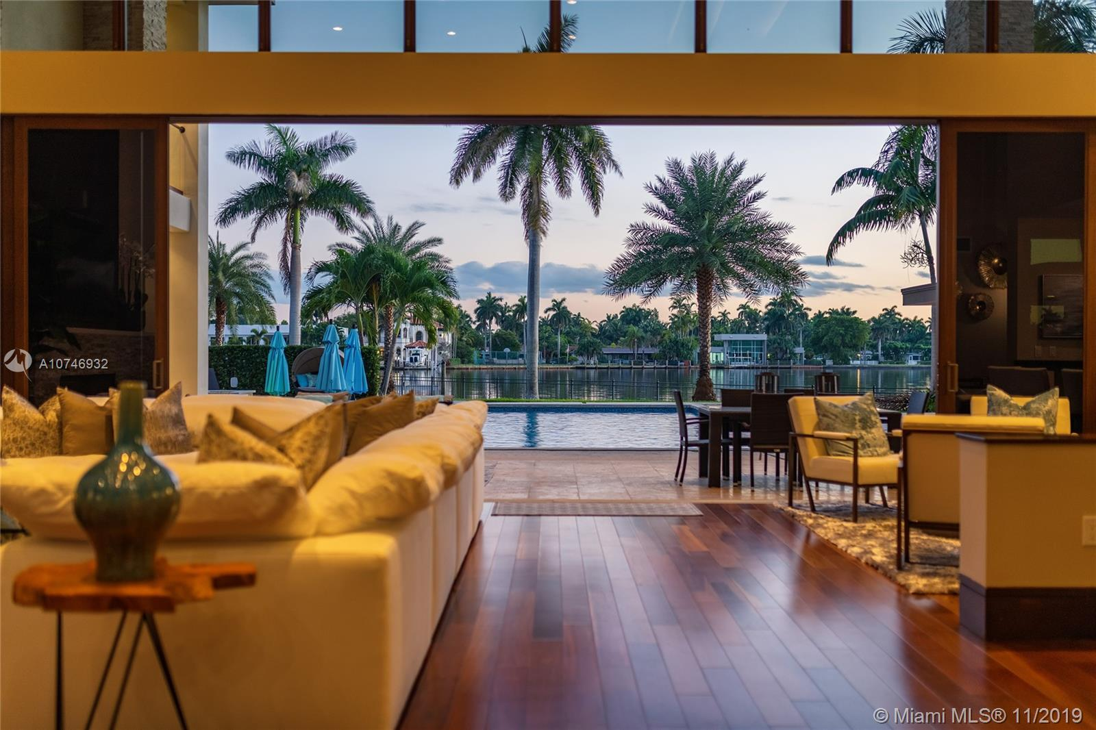 Tropical Modern Estate situated between Miami & Ft Laud. totaling approximately 8k sq. ft., 6 bedrms/6.5 unique baths w/wide water views in every room & resort-style pool w/25k lot.  No fixed bridges, large dock w/20k lbs boat lift & 160' on water.  Summer kitchen, large hot tub, tanning shelf, & fire pit, full bar, gourmet kitchen; Master has a spa bathroom,two water closets & multi-person shower.  All bedrooms have full en-suite baths & 6th bedrm is attached via covered walkway & use as a gym, office or in-law suite.  Windows & massive sliders are hurricane-impact & UV protected, the walls are concrete block construction & 2nd story has concrete floor. 5 AC zones, fireplace in living area & master bedrm & Crestron lighting systm.  3 car garage,ample guest parking in governor's drivewy.