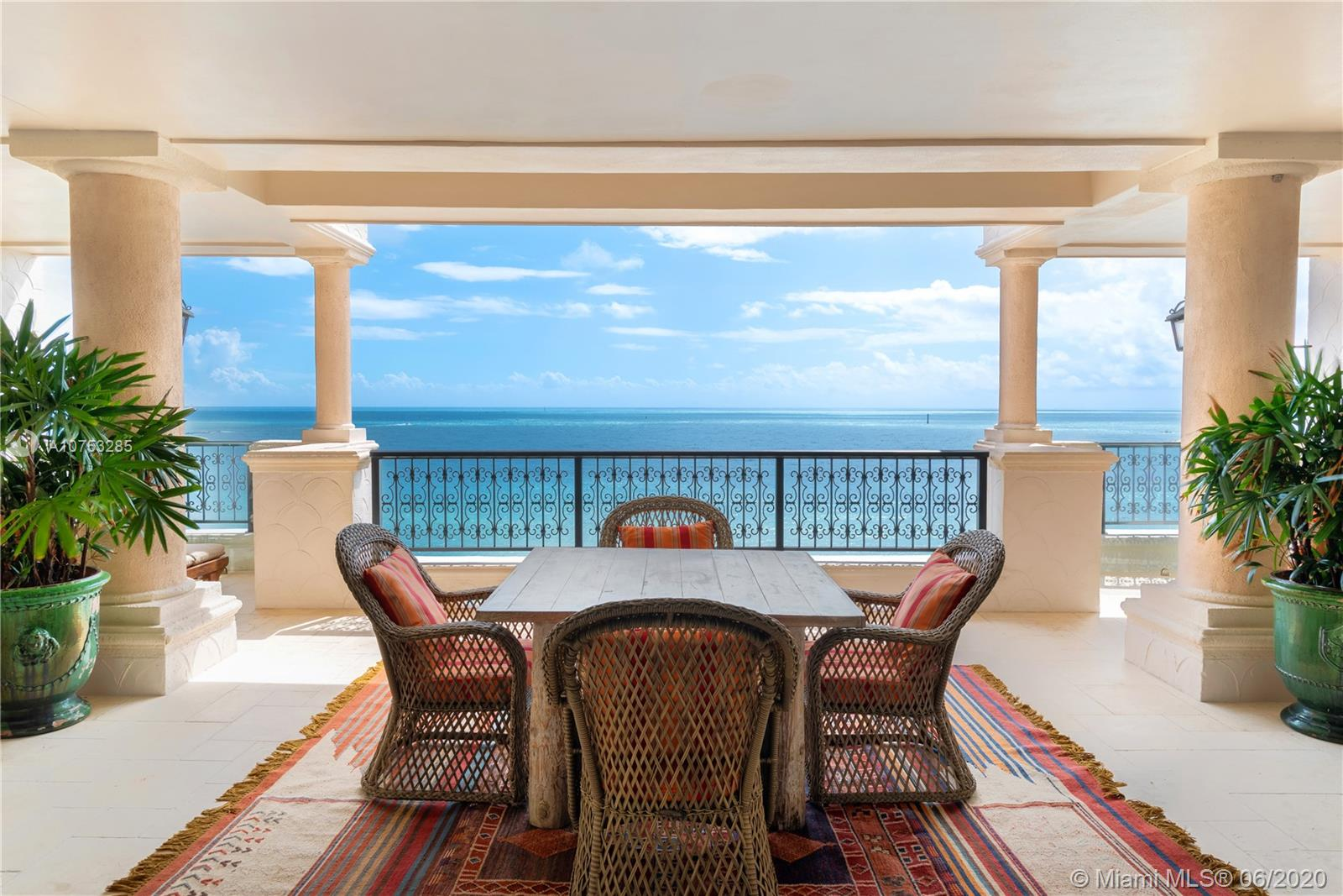 This stunning oceanside lower penthouse offers million-dollar direct ocean views. Enjoy the breathtaking Miami skyline, oceanfront views, and golf course views from every room and balcony. Boasting 5 bedrooms, 5 bathrooms, and 1 half bath, this 6,170 square foot residence offers custom features throughout. Intricate design details include a remarkable fireplace, exposed wooden beams, and custom carved wooden doors in the living room. Gourmet kitchen that features top-of-the-line Wolf and Miele appliances including a Wolf induction burner. Includes two covered garage parking spots and golf cart parking space. Wake up in your principal suite with sensational ocean views, dual closets and a private balcony. Live the ocean front lifestyle dream of Fisher Island.