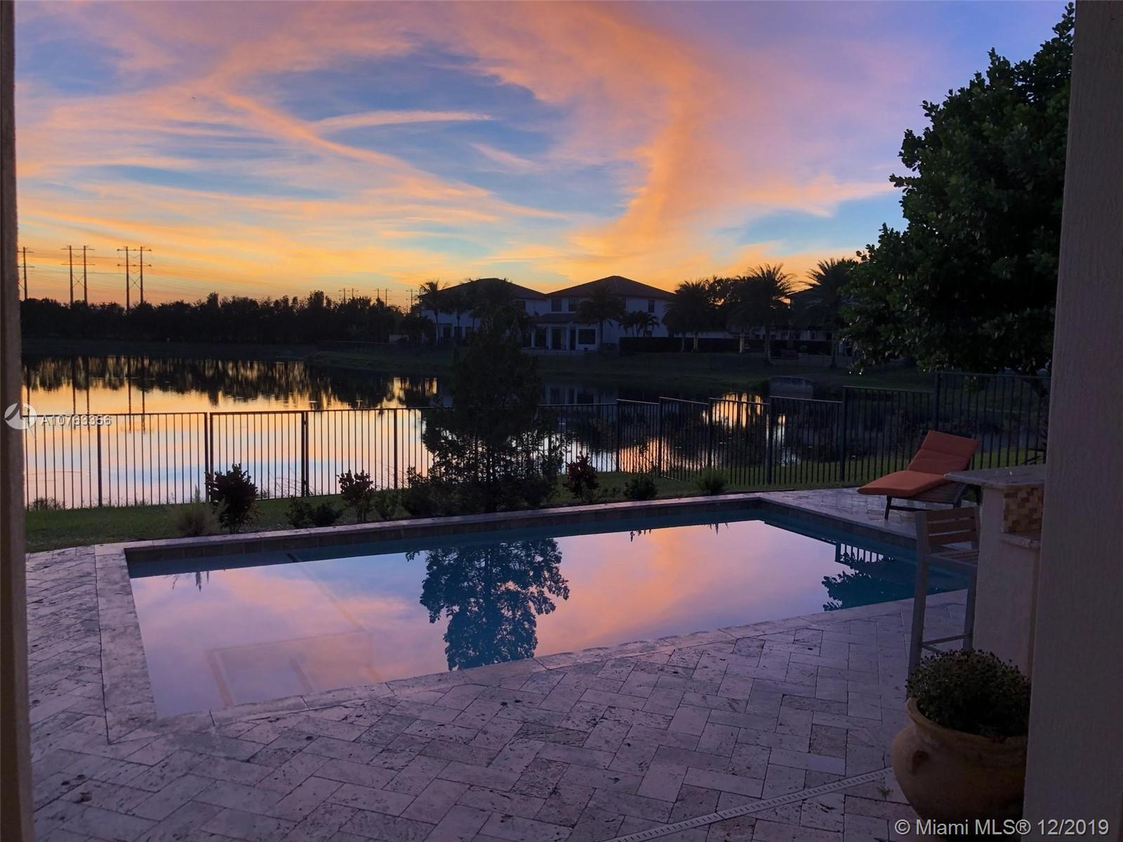 This elegant lakefront Cooper City smart home has too many upgrades to mention here. Upstairs, an 18' by 13.5' loft relishes alongside the Owner's suite which overlooks the custom built heated saltwater pool/summer kitchen. One bedroom is downstairs.  The Jack and Jill bedrooms encompass the loft as well.  Our 24 hour guard gated community boasts an extravagant clubhouse with all the amenities including seperate cardio and weight studios.  Upon your tour, you shall find a game room, bike trail, basketball and tennis courts three play grounds and two dog parks.  HOA fees are essentially included in the property taxes. Zoned for Embassy Creek Elementary.