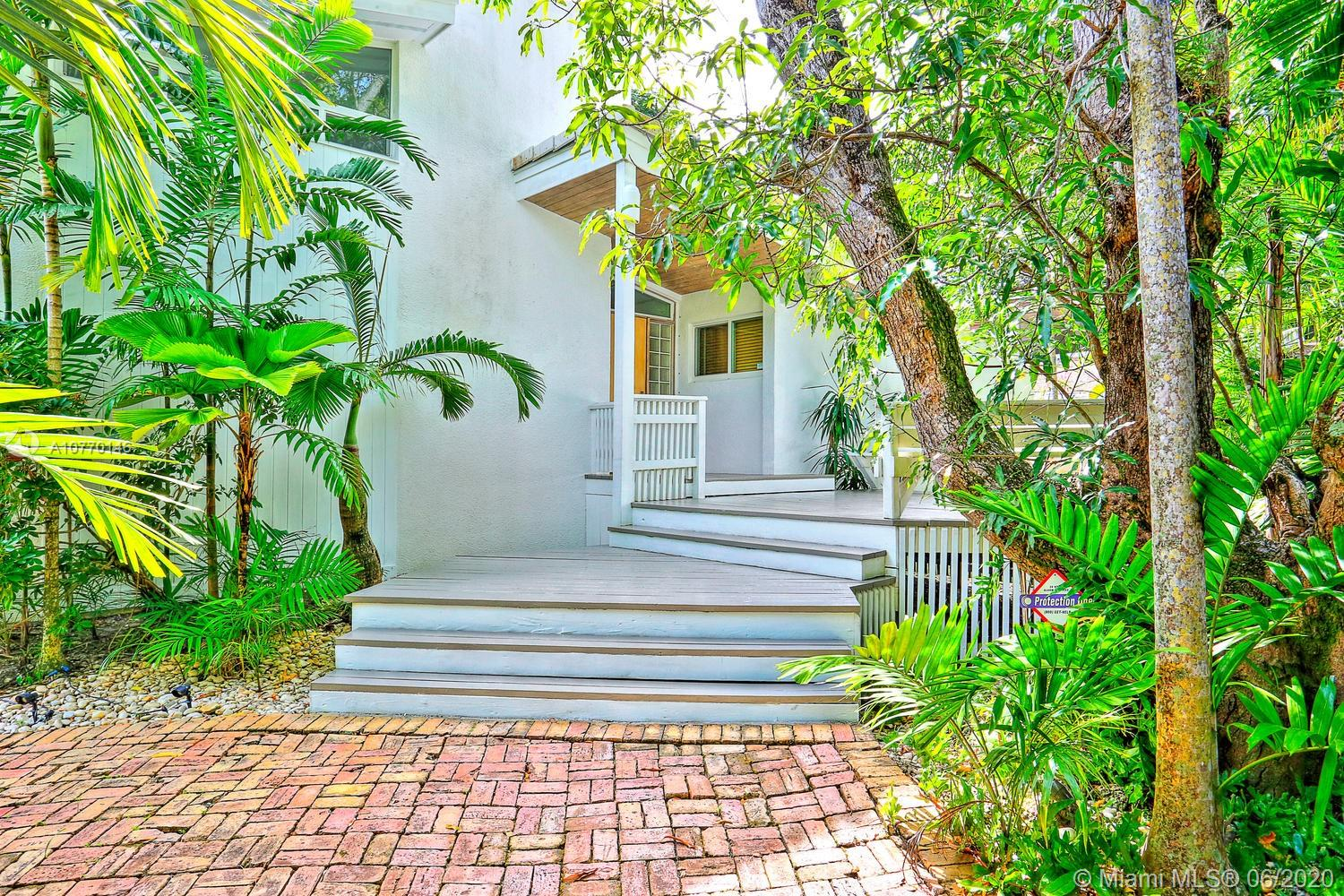 Stunning, coastal contemporary-style home set back within a lush tropical hammock of exotic palms & mature oaks. Light-filled living spaces w/dramatic, vaulted wood beamed ceilings & natural finish, wide-plank cypress flooring. Multi-level layout offers expansive living & dining areas w/walls of glass overlooking the pool & garden.Totally renovated, european-style kitchen features wood cabinetry, stone countertops, gas cooktop, double wall-ovens & wine refrigeration.Enjoy outdoor living & entertaining on the covered terrace w/wet bar that overlooks the ultra-private pool surrounded by travertine pavers.Additional renovations include: impact windows, roof, 3 new AC systems, Trex decking on roof-top terrace & wrap-around balcony. Walk to the Grove village's boutiques, cafes & bayfront parks.