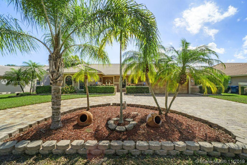 Has crown moulding, granite counters, stainless appliances, hurricane impact windows, large master bedroom with 2 walk-in closets, on interior lot with screened, heated pool & privacy hedge yard, circular paver driveway.