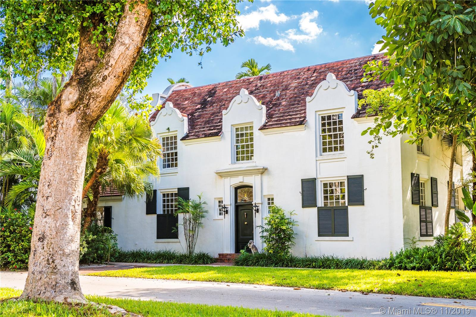 """Introducing Historic house, """"Cape Dutch"""". One of only five homes built in the 1920's in one of Coral Gables uniquely themed villages. The Dutch South African Village is a unique assemblage of homes designed by the well-knownPalm Beach architect Marion Sims Wyeth and built by Coral Gables developer George Merrick. This unique village drew inspiration from the Dutch farmhouses of those wealthy planters of Cape Town. Fewer than 80 of the1,000 planned residences of Merrick's villages were built. This traditional Cape Dutch designed home is an incredible piece of history. The home features five bedrooms and three and a half baths split between the mainhouse and the guest house in the rear, divided by the pool and spacious Veranda perfect for enjoying the serene outdoor space."""