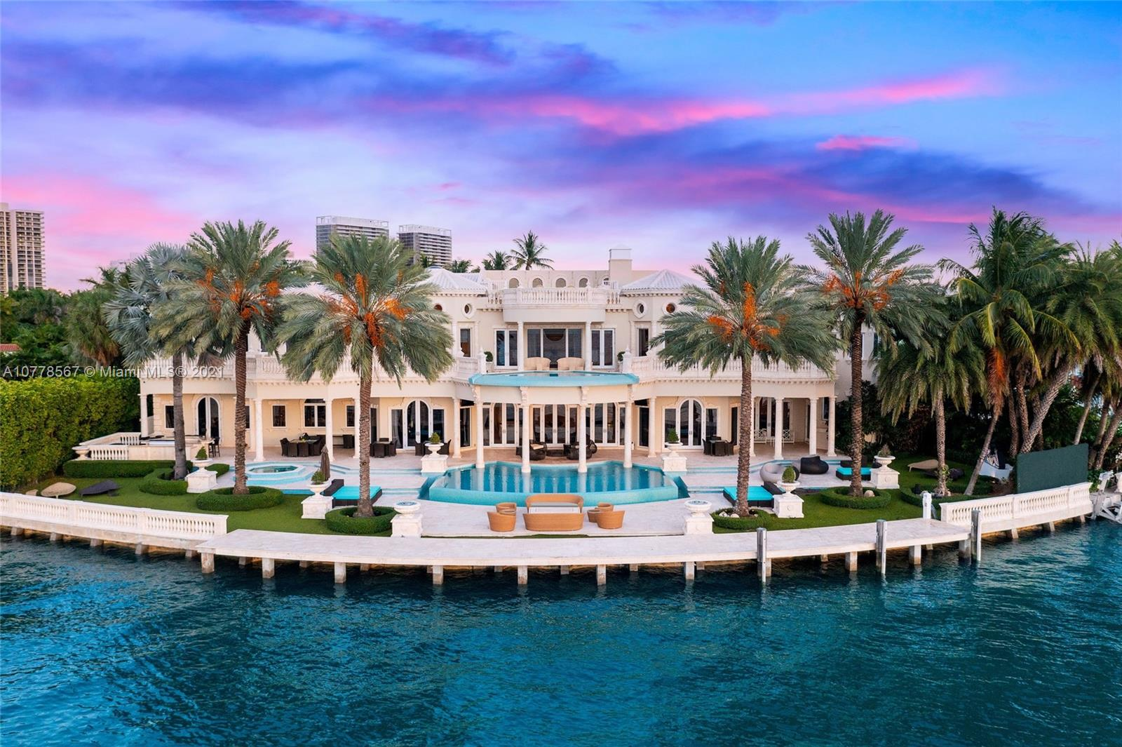 Absolutely unparalleled in finishes, appointments & furniture, this 12,879 SF palatial estate is designed like no other. Villa Magnolia sits upon 221 ft of wide waterfront with nw exposure, offering a front-row seat to dazzling sunsets. Private gates open to reveal a majestic Neoclassical home towering above verdant foliage. Enter into a rotunda foyer w/ a soaring 40-foot ceiling, curved marble & a striking two-sided staircase w/ white gold leaf bannisters. Unique features include hand-crafted stone throughout, European paint finishes, 15-foot coffered ceilings, 2-infinity edge pools, one just off the principal suite, 3rd level rooftop entertaining terrace, temperature-controlled 850-bottle wine room, gourmet kitchen w/ a built-in 750-gallon aquarium, movie theatre & glass elevator.