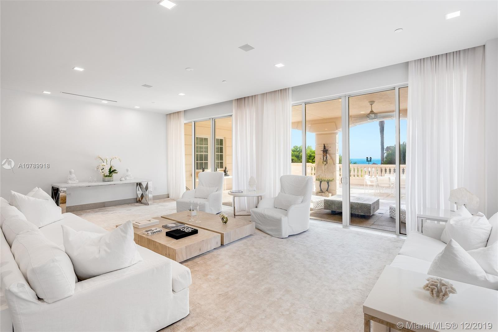 This amazing ground floor Oceanside unit on Fisher is truly luxury island living at its best. The professionally designed residence features exquisite marble & wood floors throughout, approx. 4,644 SF of spacious open layout w/seamless family/media & dining area, a pool room & formal living room w/direct access to an expansive full wraparound terrace w/beach & ocean views. The sleek gourmet kitchen sports a large granite center island w/extension for eat-in seating, Ornare cabinetry, granite counter tops & backsplash, top-of-the-line appliances. The private principal suite features voluminous separate dual walk-in closets, views to the ocean & a stunning marble bath w/oval soaking tub, walk-in marble/glass rainshower w/steam. In addition, there are 3 spacious bedrooms w/en-suite baths.