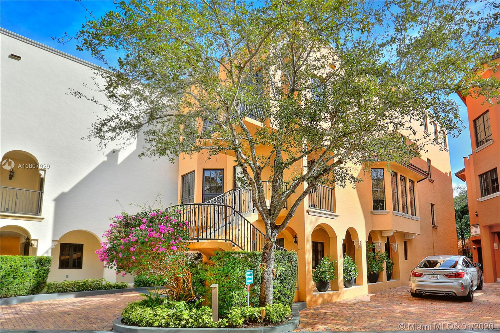 Stunning villa with a modern vibe in the exclusive, gated enclave of Cloisters on the Bay. Just steps to the Grove village center's galleries, boutiques, cafes and bayfront parks & marinas. Enter the 2nd level main entrance into light-filled, expansive living & formal dining area, private den/office and oversized kitchen w/ sleek, euro-style cabinetry & separate breakfast room. Ground level guest suite offers private entrance + large family room. Third level - 3 BR's w/ ensuite baths, including the luxurious master suite featuring a private balcony & marble bath w/soaking tub & glass-enclosed shower. Enjoy panoramic views & bay breezes from the sweeping roof-top terrace. Elevator to all levels.  2 CG. Community amenities: 24/7 guard gate, heated pool, lighted clay tennis court & clubhouse.