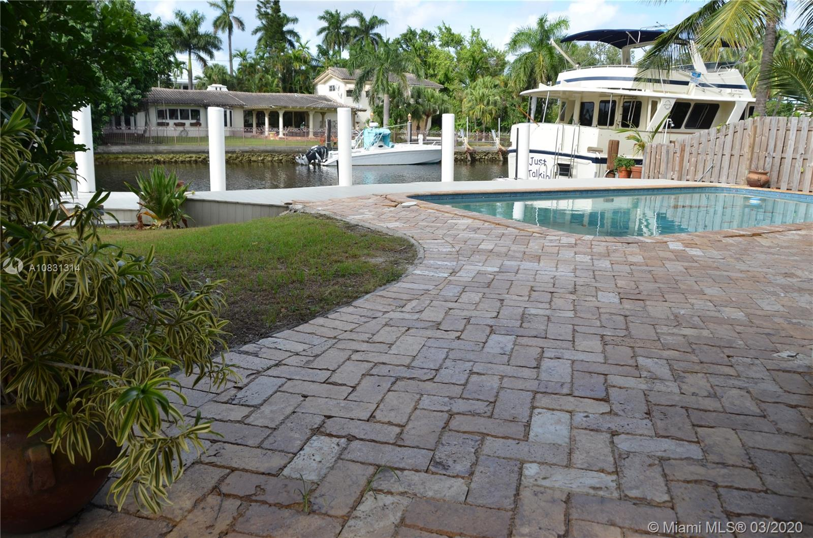 Charming Spanish Colonial Era, Seven Isles home.  Elegant 3 Bedroom + OFFICE + Video Game/TV room/ 4 Bath.  Large patio and pool, perfect for entertaining.  Three way split floor plan.  Main Master bedroom and 3rd bedroom go out to the pool and large back patio.  Second Master Bedroom goes out to a court yard that leads to the pool and dock area.  Park your boat bu the 50' long dock built on this 60' canal front lot with no fixed bridges access to Ocean.  In addition to the circular driveway there is a large parking area on the right side of the house, perfect to park more cars, motorcycles, small boats, jet skis, etc. 