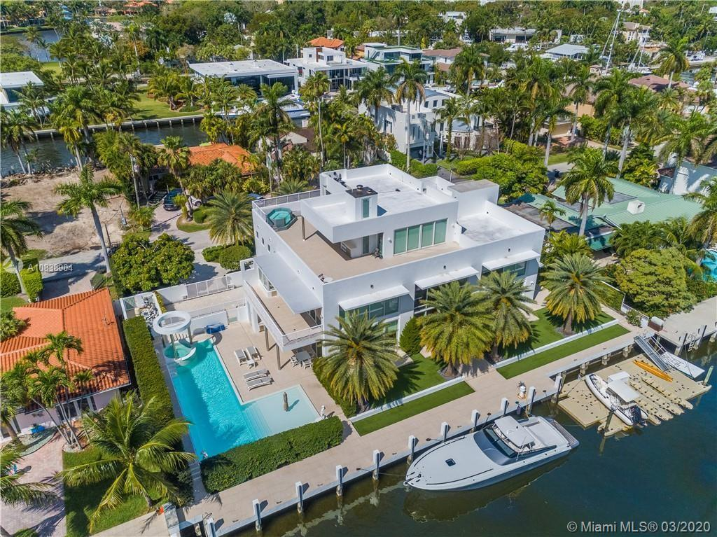 Luxurious waterfront fortress with almost 8,000 sq ft of living space along 150 ft of tiled concrete dock on a 120' extra wide canal. This heavily secured private residence is a yachtsman's playpen nestled within the prestigious Las Olas Isles. Just off the point, relax with added privacy, direct ocean access, and proximity to the beach and fine dining. The northern wing doubles as a separate apartment and office. The southern wing is flanked by an all-day sun pool with 48' lap lane, hot tub, and an outdoor kitchen. Living room boasts 22 ft ceilings, wood-burning fireplace, and provides plenty of room for entertainment. House features security and sound system throughout, glass elevator, second hot tub on the 3rd floor, half a dozen balconies, rooftop, whole house gas generator.