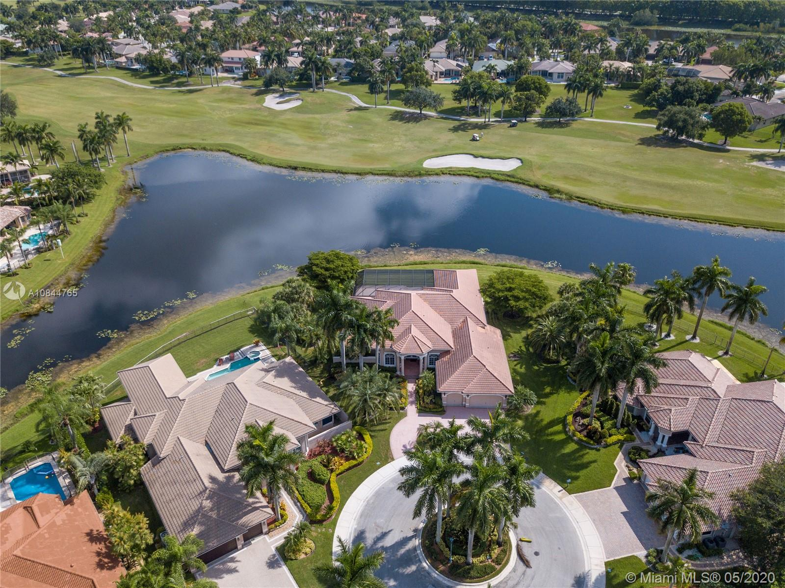 One of the most MAGNIFICENT VIEWS IN WESTON, in the PRESTIGIOUS WESTON HILLS COUNTRY CLUB. HUGE OVERSIZE LOT with 27,000 sq ft and 180-DEGREE BREATHTAKING LAKE AND GOLF VIEWS. Located in a CUL-DE-SAC in the premier section of Poinciana. Live the perfect lifestyle in this spectacular home, with an open concept floorplan and very high ceilings. Windows in every room allows for beautiful natural light and gorgeous views throughout the home. Very tranquil and private outside area, with a huge screened pool/patio enclosure. Master suite with spacious custom closets and a special feature: His and Hers master bathrooms. Accordion shutters. Access to excellent A-RATED PUBLIC SCHOOLS. RENDERINGS WITH PROPOSED DESIGN INCLUDED. THIS PROPERTY IS UNIQUE AND A MUST SEE!