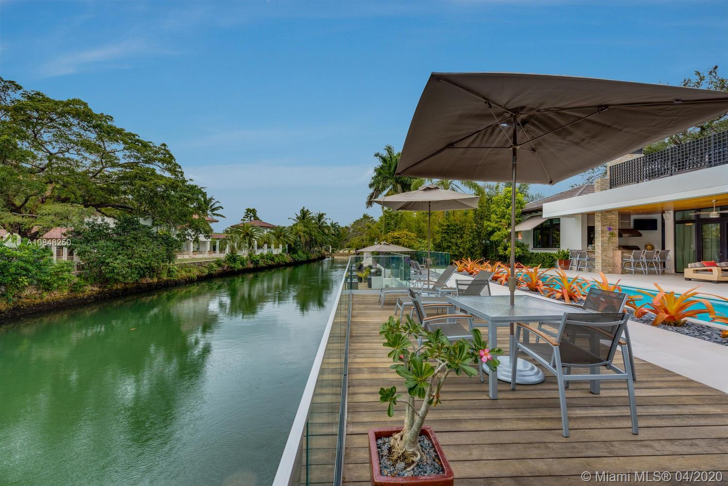 Beautifully designed Coral Gables waterfront home by award winning Ramon Pacheco. This exquisite residence was built in 2014 and features Cantilevered boat dock for a 36ft boat, heated & salt water pool and spa, large terrace with fully built out summer kitchen and surround sound system makes for amazing outside entertainment! Interior features includes custom built kitchen with built in TV,  soaring 14 ft ceilings and marble floors throughout. The Master suite is light-filled with views of the garden, canal and pool area, featuring a very large master bathroom with double sink with quartz counter tops, double shower, double closet and a morning kitchen with refrigerator. Landscape & irrigation system designed by renowned landscape and golf course Architect. Virtual tour available!