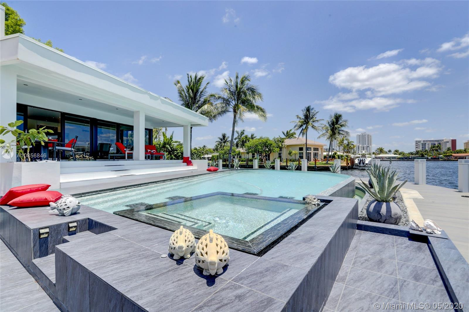 Hidden gem in Pompano Isles with breathtaking views on the Intracoastal and intersecting canals. As soon as you walk in, you will see impressive water views from everywhere inside this beautiful modern house. This private & peaceful property features 190 feet of waterfront point lot with 180 feet of composite dock. This is the perfect boaters paradise. The master bedroom suite is upstairs with private balcony & the guest room is downstairs for more privacy. The kitchen, living and dining opens to a large patio area great for poolside lounging & entertaining all year long. Infinity pool with salt chlorination system & spa for more pleasure. Conveniently located near the Hillsboro Inlet, no fixed bridges, ocean access, sun all day with pool facing East. This house is aboslutely perfect!