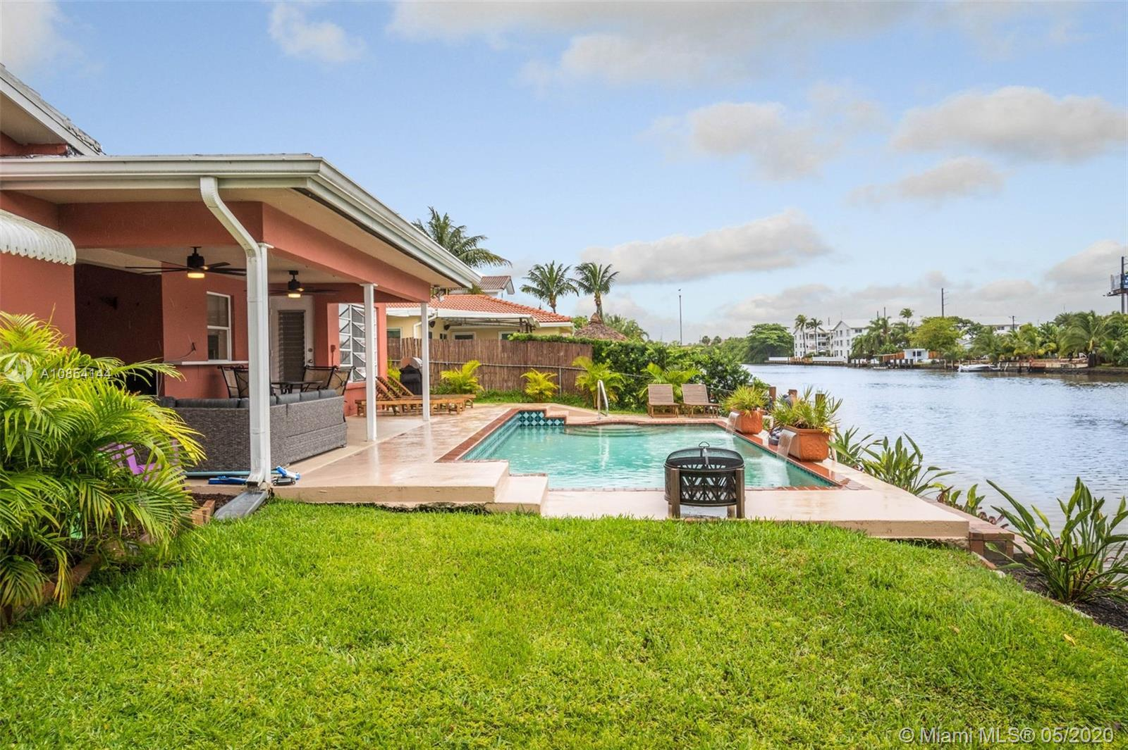 Located on Wilton Manors' ONLY private gated island, this mid century modern home sits on 80' of waterfront overlooking the 200' wide Middle River, w/ dockage for a small boat, glistening pool & large covered patio area. Ideal northern exposure w/ constant backyard breeze. Waterfront, pool & backyard views from Family Rm, Kitchen, Dining Rm & Master. Both bathrooms recently updated; Master w/ marble vanity & flooring, & guest bath w/ subway tile & dual vanity. Permitted repairs completed, including replacing all underground plumbing, sewer & water lines, & updated electrical panels. 2012 AC. 1 car garage, extra wide paver drive. Bright, open concept in amazing location, minutes to i95, Mills Pond Park, & zoned A Rated Wilton Manors Elementary. Virtual Tour https://bit.ly/2TbPFDx