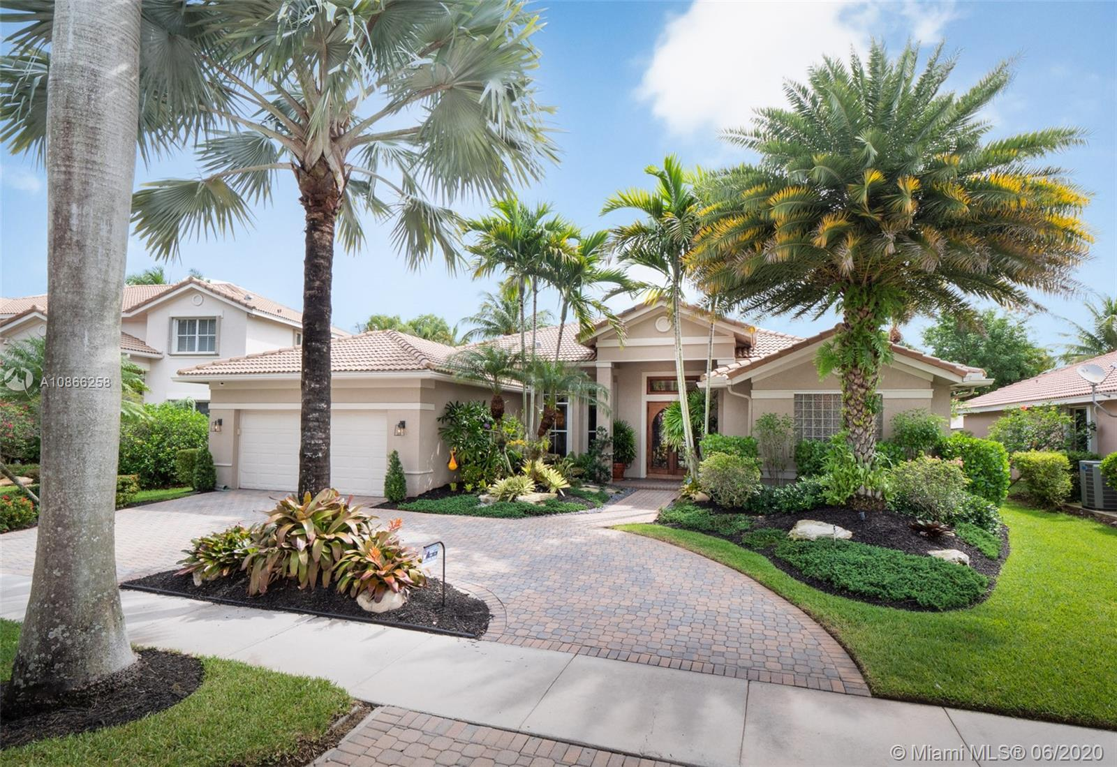 Custom home tucked on a royal palm tree-lined street with a circular paver driveway.  Popular triple split floorplan  Shows like a decorator model.  New Kitchen with top of the line Stainless Steel appliances, granite countertops. Neutral stone tile throughout living areas.  Extensive crown moldings, coffered ceilings, stunning custom window treatments, and drapes. All bathrooms renovated. Private fenced yard with a resort-style freeform pool and paver patio. Lush tropical landscaping. Walk to community park.