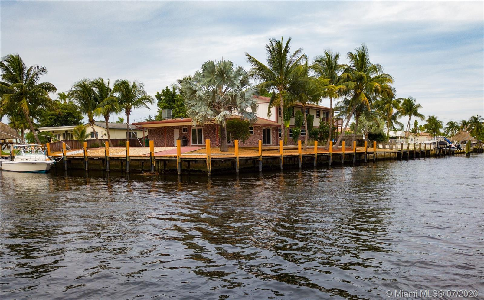 Boater's delight, corner lot with 220' of WATERFRONT and 180' of DOCK on the Dania Cutoff canal & only 1 fixed bridge. CLICK ON VIRTUAL TOUR.One-of-a-kind 2 story home with 4 beds/3.5 baths plus a huge library/den and an oversize 2-car garage. Grand double front door entrance walking into living room with 18-foot ceilings, gorgeous custom-built kitchen with stainless steel appliances, granite counter tops and beautiful tile back splash and bar-top overseeing an open floor plan to family-dining room.This house is UNIQUE in many ways. IT has numerous exterior entrances, 2 porches, so you always have a cool breeze, side parking for a large trailer or RV, parking for 8 cars, very private being in the back of neighborhood on a dead-end road with limited view of neighbors. No HOA Fees.