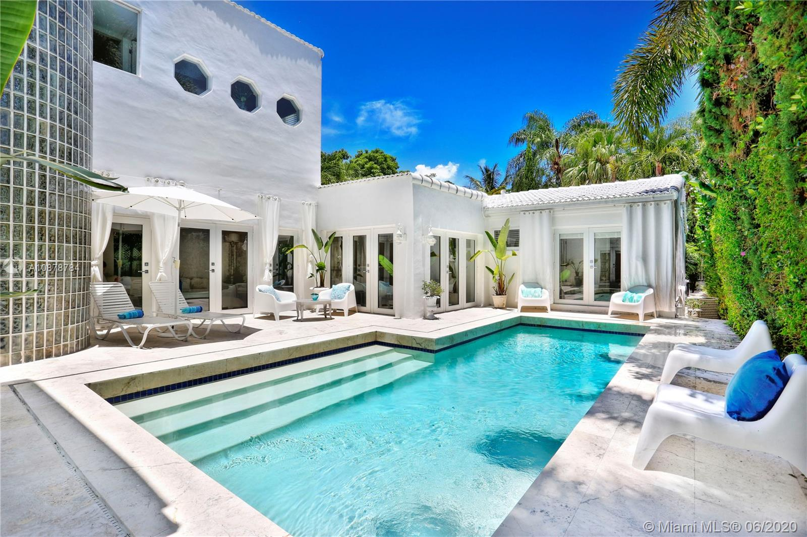 Ultra-private & serene retreat on a quiet tree-lined street in prime South Grove location. Stunning, light-filled living spaces w/ high ceilings & white-washed oak flooring. French doors throughout, overlook tranquil pool & lush tropical gardens & terraces that surround the home. A white color-palette provides the ideal backdrop for art collections. Renovated, custom kitchen opens to adjacent breakfast area. Formal living, dining & family rooms as well as two master suites (one up & one down) each w/ private sitting areas and luxurious baths w/ soaking tubs. Gated, covered parking for 2 cars + guest parking for 3+ cars. Walk to the Grove village center's, boutiques, cafes and bayfront  parks & marinas. Also just minutes to downtown Coral Gables & South Miami world-class shopping & dining.