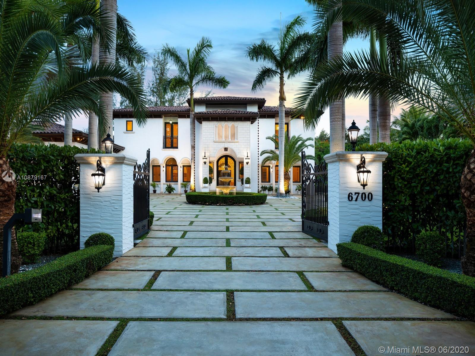 Extraordinary one acre + estate located in South Miami. Surrounded by manicured and pristine landscaping, this stunning corner property lies behind private gates showcasing an exquisite entrance and water feature. Greeted by a grand foyer and a splendid staircase, discover an open and spacious living room, dining room, custom designed kitchen with wet bar, temperature-controlled wine cellar, and family room. Elegant master suite with spa like bath and private terrace overlooking the outdoor oasis. Outdoor living awaits with a great veranda, ample lounging space with a fully equipped summer kitchen offering stunning views to the pool and spa, enjoy bountiful tropical fruit trees and ample green grounds. Extra Features: office/game room, elevator, 3 car garage.