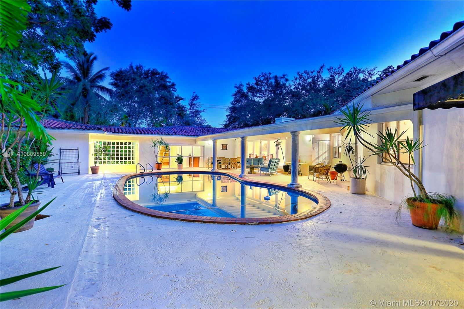 This lovely, spacious, & well maintained 4 bed/4 bath corner home with pool nestled in South Coral Gables sits on a half-acre lot (19,200 sq ft lot). With an open living to dining area featuring wood high ceilings, it naturally flows out to a spacious terrace accessible from many points. Features: marble & wood floors, fireplace, split floor plan, an oversized 2-car garage equipped with an electric vehicle charging station. Updated kitchen with s/s appliances, granite countertops, breakfast nook & an adjacent laundry room. The Family room has a built-in wet bar & an updated bathroom. The Master Suite has 2 large walk-in closets. Two of the bedrooms share a Jack & Jill bathroom. The lush backyard has a built-in deck surrounding beautiful gumbo limbo trees, perfect to relax & entertain.