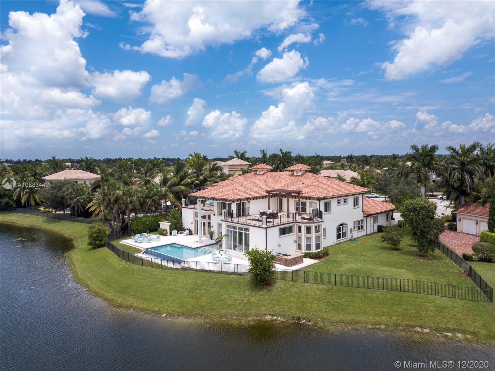 The Ideal Estate built in 2016 on arguably the best waterfront lot with open Golf Course views in the exclusive gated Heron Estates division of Heron Bay community with no rear neighbors. This unique home boasts an expansive smart layout with a grand entrance, dramatic staircase & sprawling living areas. Featuring 7 bedrooms with a large private master suite, 6 full baths and 2 half baths, separate office, additional upstairs family room, maid's quarters with oversized laundry room and more. Enjoy panoramic views from every room with floor to ceiling impact windows and over 1,500 sq ft in outdoor terraces. Experience unmatched sunset views lounging by the infinity edge pool & outdoor kitchen area. It is truly a must-see on a half-acre peninsula-shaped lot situated on a private cul de sac.