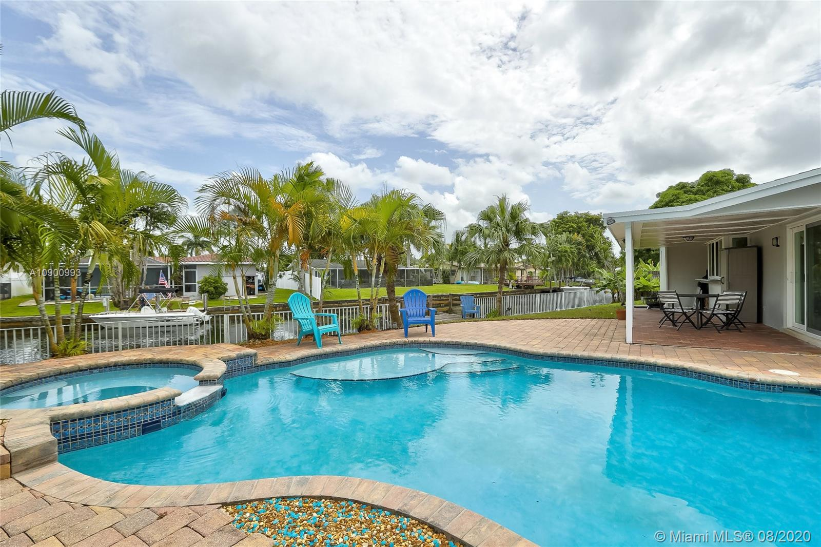 The perfect Florida Bungalow awaits!  This home offers 100 feet of water frontage with Ocean Access.  Brand new, complete impact windows with transferable warranty, fresh paint inside and out, all new pool equipment, new appliance package, updated bathrooms, as well as a newer A/C.  Expansive outdoor space with ambient lighting in addition to the free-form pool and hot tub make this the perfect Oasis for boaters, snowbirds, or investors looking for a vacation rental.  NO HOA so you can store your boat or RV on premises.  Conveniently located with easy access to I-95, beaches and shopping.