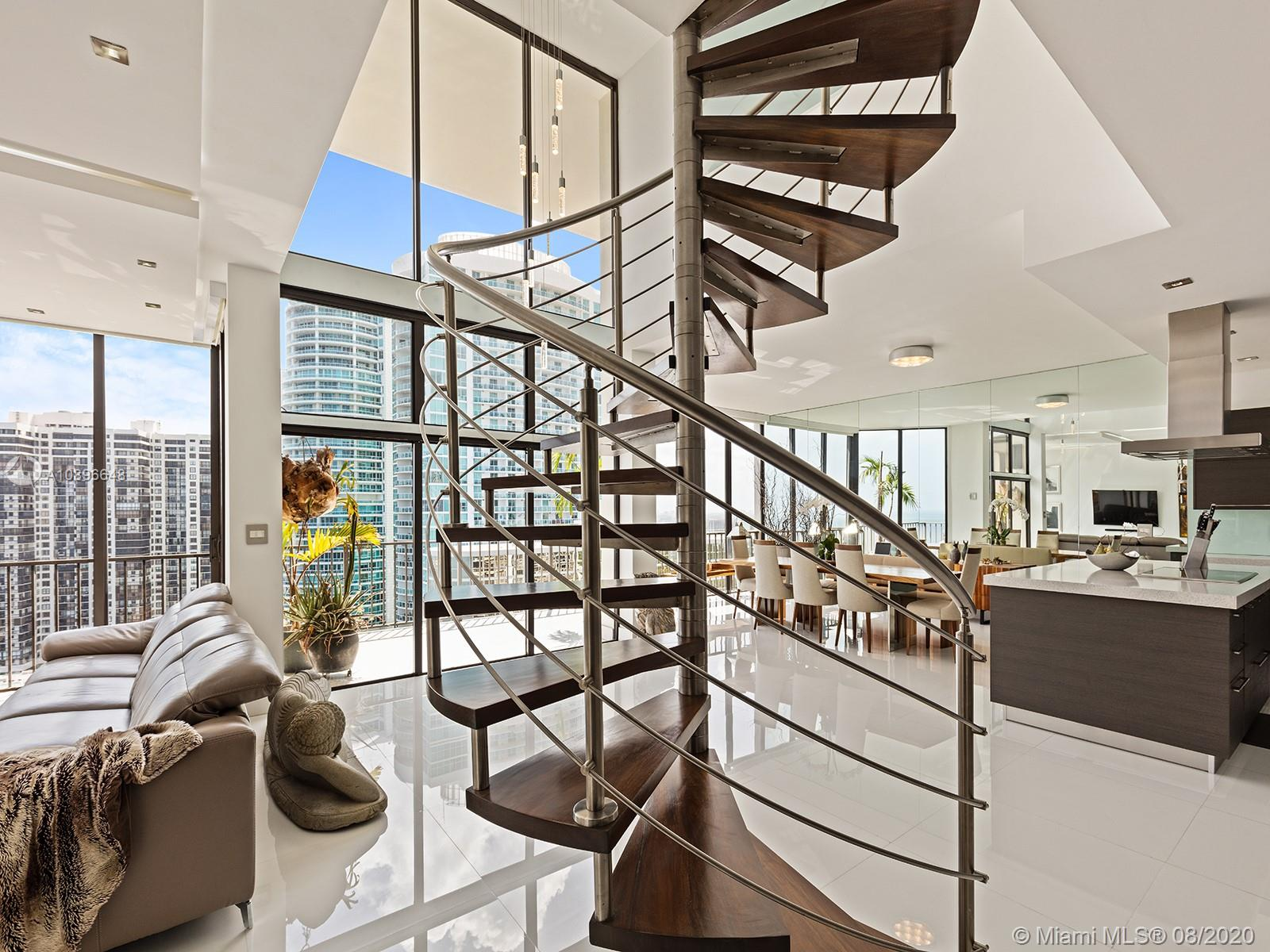 2 story Brickell PH with 22' ceilings with unobstructed wide views of the ocean, bay and city. An impressive custom stainless steel and mahogany circular staircase connects both floors. Custom curved wall and custom designer doors and closets. Open island kitchen is furnished with Thermador appliances to cook while viewing the entire bay. 2nd story marble suite overlooks the bay and allows you to soak in a Zen tub or enjoy the invigorating double rain shower with water views.  Pool, pool cabanas, Jacuzzi spa, kiddie pool, playground, tennis, racquet & basketball courts, exercise room, party rooms, marina and a wonderful BBQ area on the water's edge. Owner owns two slips that are