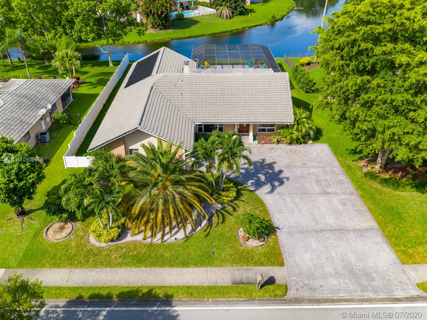 LOCATION, LOCATION, LOCATION - AND A BEAUTIFUL, WATERFRONT POOL HOME TO GO WITH IT!  MIRACULOUS 4/2.5 with MASSIVE Living Areas and Den, Working Hot Tub and Heated Pool, Giant Lot IN THE MIDDLE OF EVERYTHING!  WALKING DISTANCE to Atlantic and University, PUBLIX, SAM'S, HOME DEPOT, BEST BUY, DUNKIN, STARBUCKS RIGHT Down the Street!  HUNDREDS of Stores and Restaurants surround this Tranquil Pool Home with IMPACT WINDOWS & IMPACT GARAGE DOOR, A+ wind rated!  Heated Pool with Salt Water + Solar system, MASSIVE Living Area, WORKING FIREPLACE, Large Rooms & Tons of Storage in the Garage.  Too Many Updates to List, CANAL VIEWS, PARK OVER 12 CARS IN THE DRIVEWAY!  Screened in Patio and Pool on a Large Lot gives you the Ultimate Florida Lifestyle with EVERYTHING YOU NEED within a 5-minute Drive!