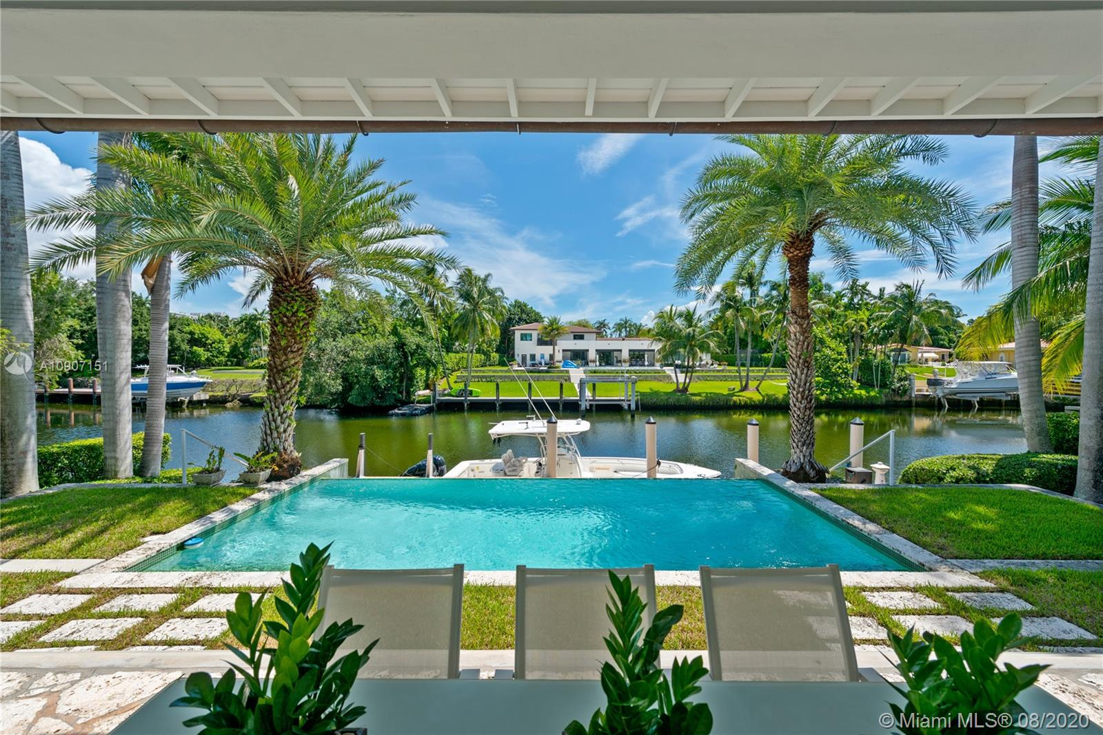 The waterfront home you've been waiting for is now available! Situated on a wide portion of the Mahi waterway in the South Gables, this one-story home was beautifully updated indoors and out. An open concept floorplan allows for water views from almost every room in the house, maximizing enjoyment of the waterfront lifestyle. A new kitchen features large chef's island, custom cabinetry & Thermador appliances, including a gas stove. Wall-to-wall glass doors open to the covered patio, built-in summer kitchen and sparkling infinity pool that appears to flow right into the canal. 3 bedrooms & 3 full bathrooms, including a master suite w/private sitting room overlooking the water. Brand new dock with concrete caps to accommodate a boat lift, impact windows & doors throughout, 2 car garage.