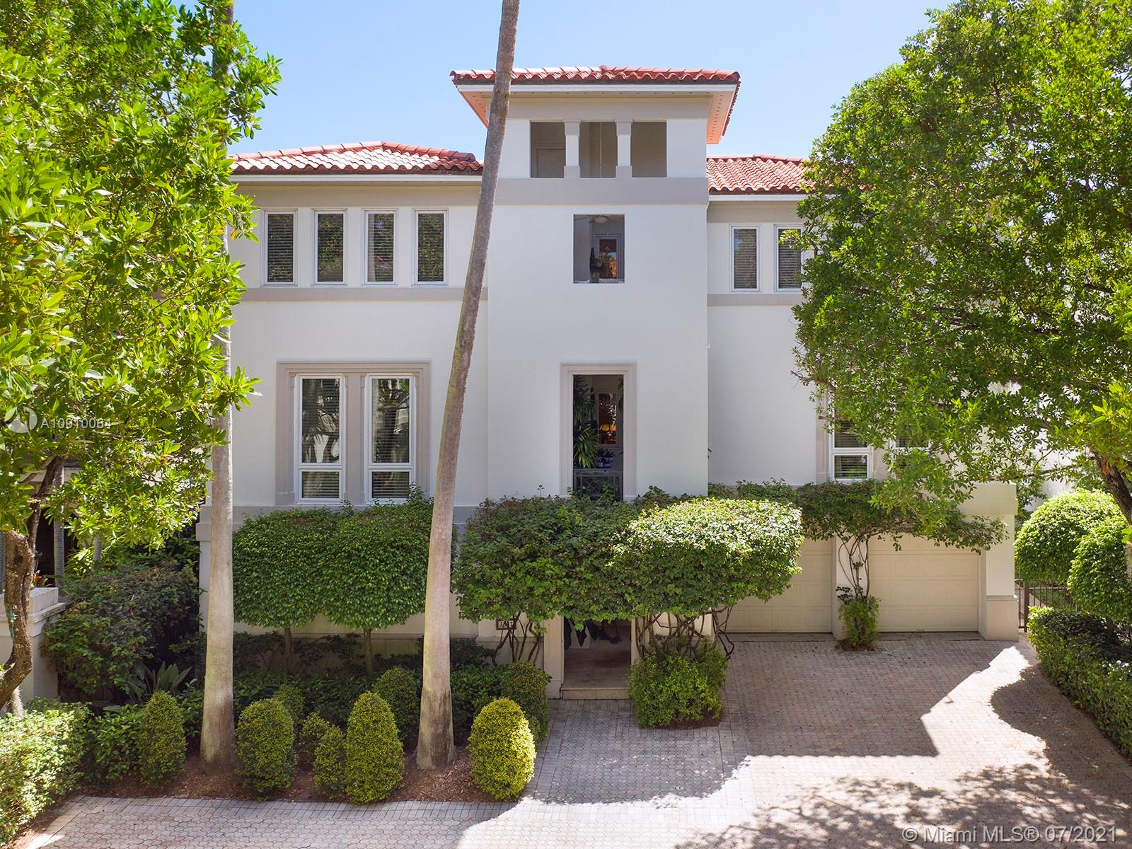 Set in private, gated Bayshore Villas tree-lined enclave of Coconut Grove, this unique NYC-style three-story home features two balconies and a two-car garage. Greeted by a three-story foyer leading to an aesthetic, serpentine happel stone stairway, the ground floor, in addition to maid room and washroom, also holds a movie theater with a 99 in screen with full bathroom overlooking a screened-in pool room and back yard that welcomes sunbathing and outdoor dining. The elevator or stairway lead to the travertine marble and happel stone-lined middle floor where floor-to-ceiling windows light up the elegant, spacious living room and dining room. Adjacent, a cozy library/sitting room connects to the huge Jenn Air/Subzero-equipped  kitchen, half bath and breakfast nook.