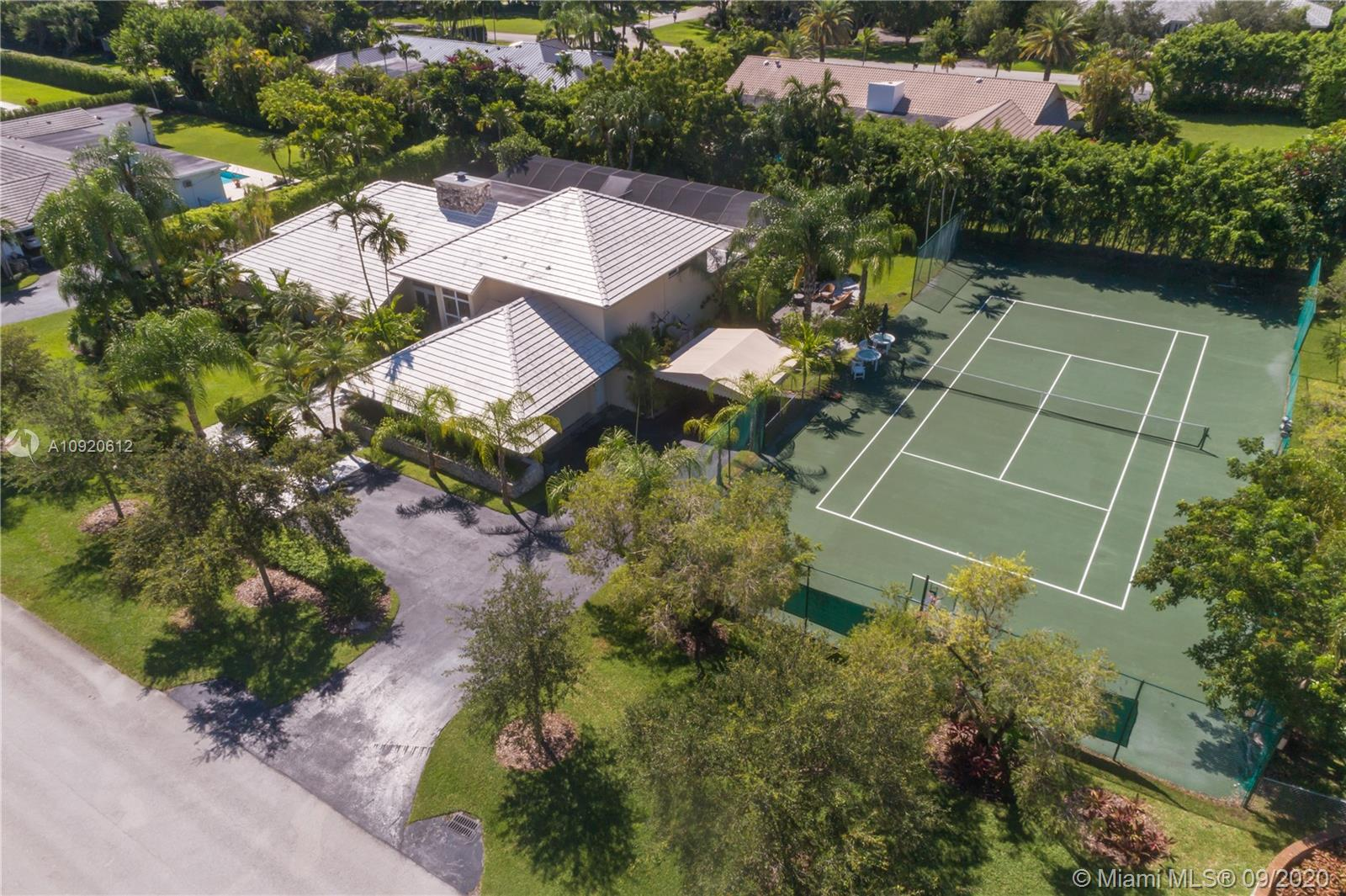 """North/South Tennis Court home in Pine Bay Estates! Resort style family retreat in premier Gables/Pinecrest. Light filled 5/3.5 + """"bonus room"""". Full home generator, new impact windows & doors, 2016 roof, 3 new zoned A/Cs. Designed for entertaining, indoor/outdoor living with summer kitchen, full bar, fireplace, and newly surfaced pool. Children's wing includes 4 bedrooms, 2 baths. Private, spacious upstairs master suite with treetop terrace overlooking tennis & basketball court. 24 hour patrolled neighborhood security. Next to Old Cutler bike trails, Pinecrest parks, and coveted private and public schools."""