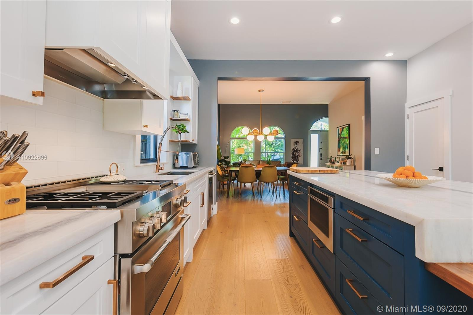 This 2 story tropical paradise in the heart of Coconut Grove can be yours! 4 Bedroom, 2 ½ bath pool home. The main floor features eat-in remodeled custom wood Chef's kitchen with gas stove, Jenn-Air appliances, quartzite counter tops, integrated refrigerator, built-in natural walnut dining table, coffee bar area with wine fridge. Italian White Oak wood floors throughout first floor and bedroom. Large laundry room with storage. The outdoor entertainment space encompasses a  covered terrace, travertine pool deck, jacuzzi, Argentinian style BBQ charcoal/wood grill and luscious landscaping. Security cameras throughout property. 2 Electric vehicle charging stations. Walking distance to parks, bay, shops and restaurants.
