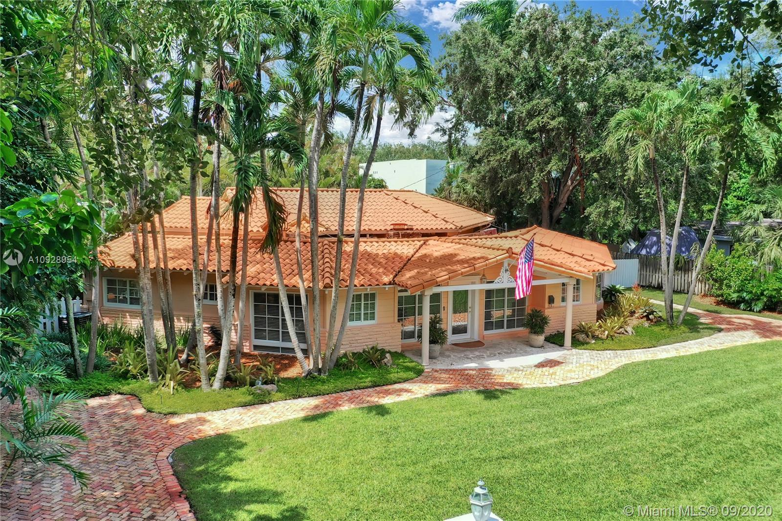 """This cottage-style charmer is located on a quiet, tree-lined street in the beautiful Ponce Davis/High Pines neighborhood. The home features high volume ceilings w/ exposed beams, marble/wood flooring, & new impact windows & doors. The light & bright, wide-open living spaces open to a lushly landscaped tropical waterfall, pool/patio oasis, w/Jacuzzi, & spacious gazebo for entertaining. Other details include 6"""" base/crown molding, Waterworks bath fixtures, 2 New A/C's, city water & septic. Close to favored South Miami/Gables/Grove, parks, shops, restaurants, & top schools. Come fall in love with this charming, tropical home within one of Miami's most sought after neighborhoods."""