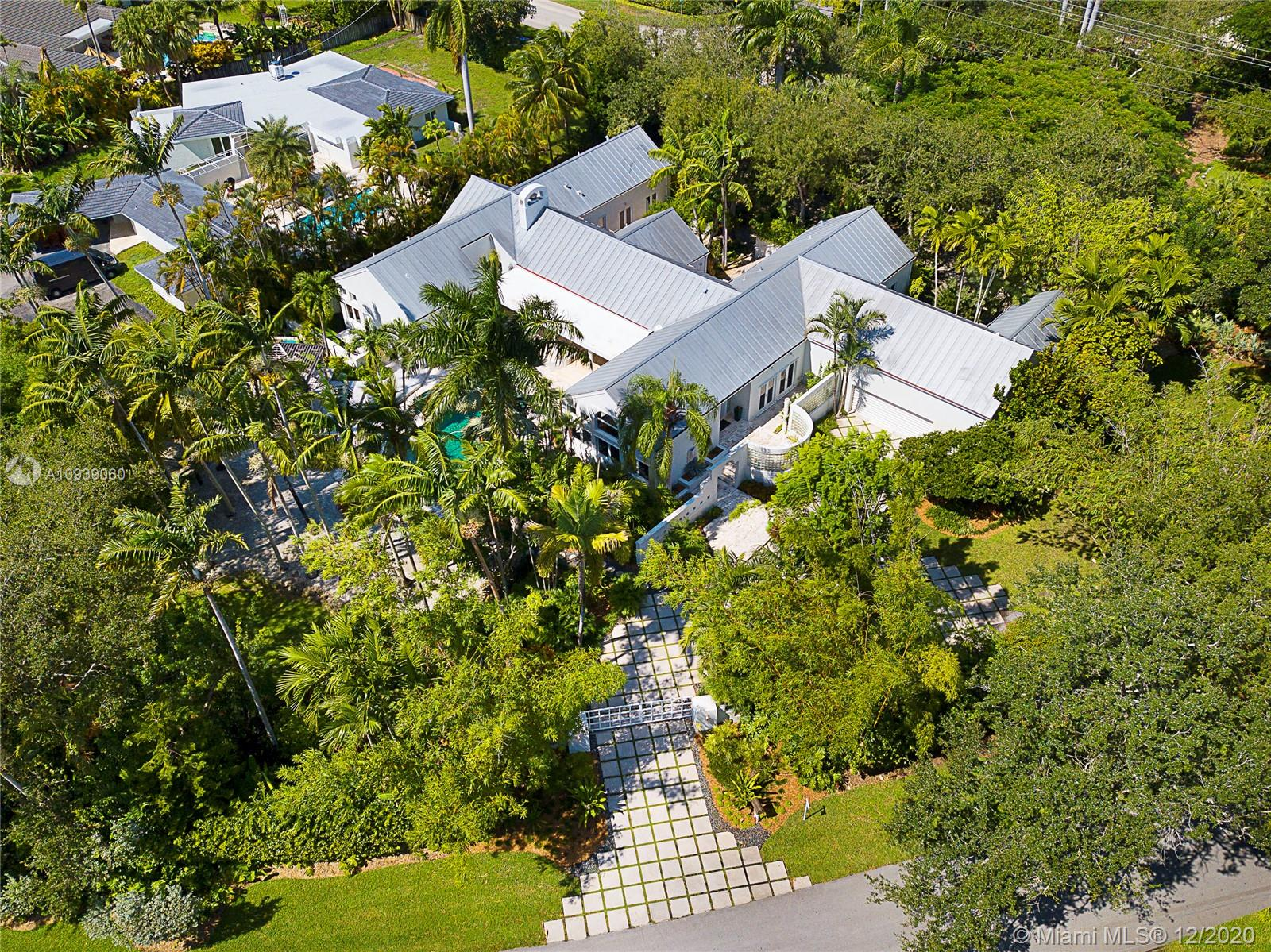 Situated on a lush acre w/ beach like design by Robert Parsley, this 6 BR, 7 BA 5,858 sq ft contemporary is an oasis in the heart of Miami!  Courtyard entrance leads to gracious formal liv & din rms w/ vaulted ceilings & oversized windows that give the space beautiful light & a sense of grandeur.  That feeling continues into the chef's kitchen w/ professional appliances open to the fam rm w/ fireplace, bar, banks of French drs & transom wndws. The split BR plan features master suite w/ sitting rm, large BA & 2 walk-in closets + 2 brms & baths to one side, 2 add'l BRs w/ en-suite BAs on the opposite side, + staff BR or man cave.  This 1-story home in a soon-to-be-gated community is the perfect opportunity to live in Coral Gables w/ access to the best schools a stone's throw away!