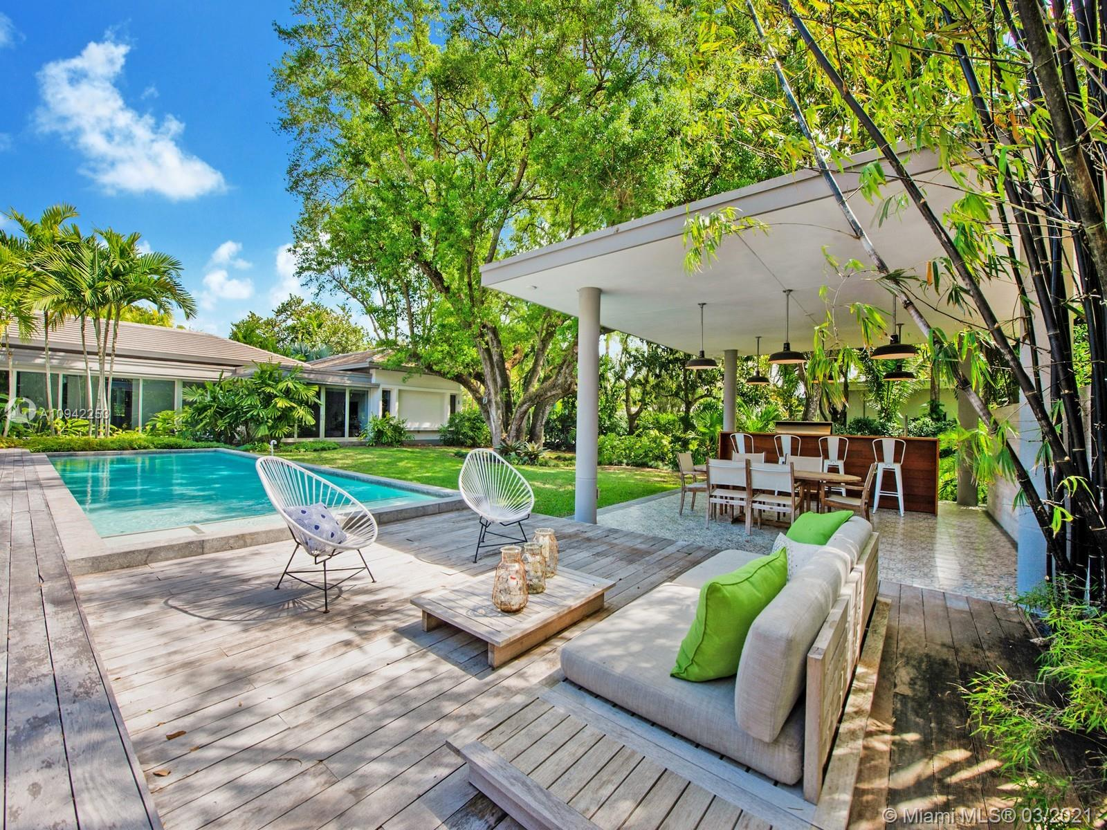 Custom Built Mid Century-Tropical Modern estate located in N Pinecrest. A tropical paradise nestled on a 34,717 sf lot enveloped by lush landscaping. Greeted by a boundless flr plan w/exquisite finishes & endless all-around views of the gorgeous backyd oasis w/huge windows & doors, providing bountiful natural light. The open flr plan offers a spacious living & dining rm w/high ceilings & integrated spaces. Custom Chef's kit w/Thermador Appl, gas range, breakfast area & huge family rm great for entertaining family/friends. Main Bedrm offers walk-in closet, patio area, spa-like bath w/shower, floating tub & double vanities. Media rm located outside main & secondary bedrms. Add features: poured Concrete Roof, service quarters, limestone & wd flrs, resort pool, summer kit, 2 car gar. Must See!
