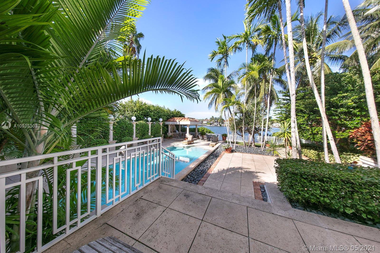 Live in paradise in this mediterranean-inspired waterfront estate located in exclusive community on Palm Island! Architecturally designed w/ large windows providing natural lighting, this 5 BD/4.2 BA home has open floor plan w/ spacious indoor living & covered outdoor living areas, surrounded by beautiful lush landscaping. 100FT of water frontage. Features include a dramatic foyer w/ soaring high ceilings, a grand living room w/ fireplace & 1800's chandeliers, dining & breakfast spaces, unique cow-bone kitchen cabinets imported from Colombia, Oak Wood floors, an African Rosewood Media Room, a corner office, a bar w/ built-in aquarium, a master suite w/ 2 balconies, & more! Enjoy stunning views from a comfortable terrace, relax inside pool surrounded by lion-shaped fountains, & private dock