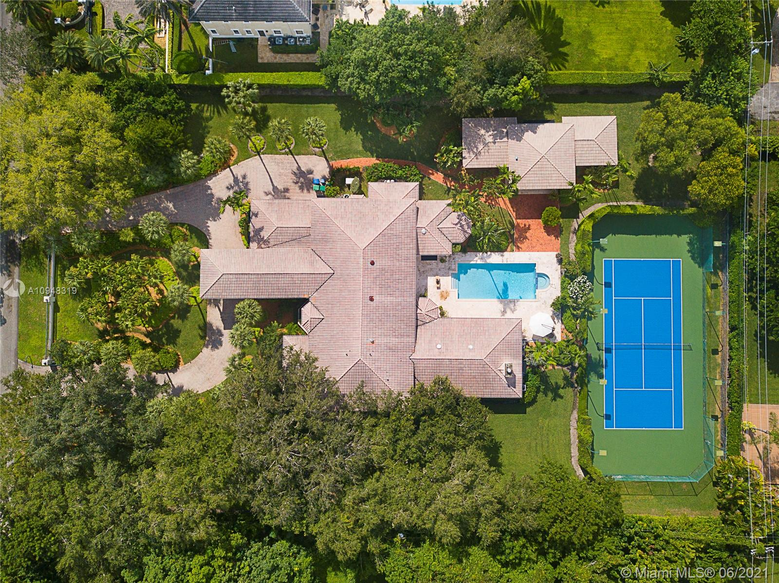 Situated on a prestigious street in Pinecrest, find this custom-built home that sits on a 61,000 sf lot & boasts 8,500+ sf. The impressive home is set back nicely from the street w/ electric gates & circular drive. Enter from its grand porte-cochere to the foyer brilliantly overlooking the formal liv & din areas. Built in 1991 it boasts generous entertaining spaces inside & out, high ceilings, built ins, all impact glass, lit tennis ct, 5 BR+ office inside & 2 outside BRs as part of pool house w/ summer kit, oversized fam rm w/ wet bar, plantation shutters & too much more to mention. Outdoor covered spaces serve as add'l liv areas. Gracious principal suite w/ sitting area, updated bath w/ double vanity, freestanding tub, large shower, dressing rm & 2 walk in closets. 3 car gar, laundry rm.