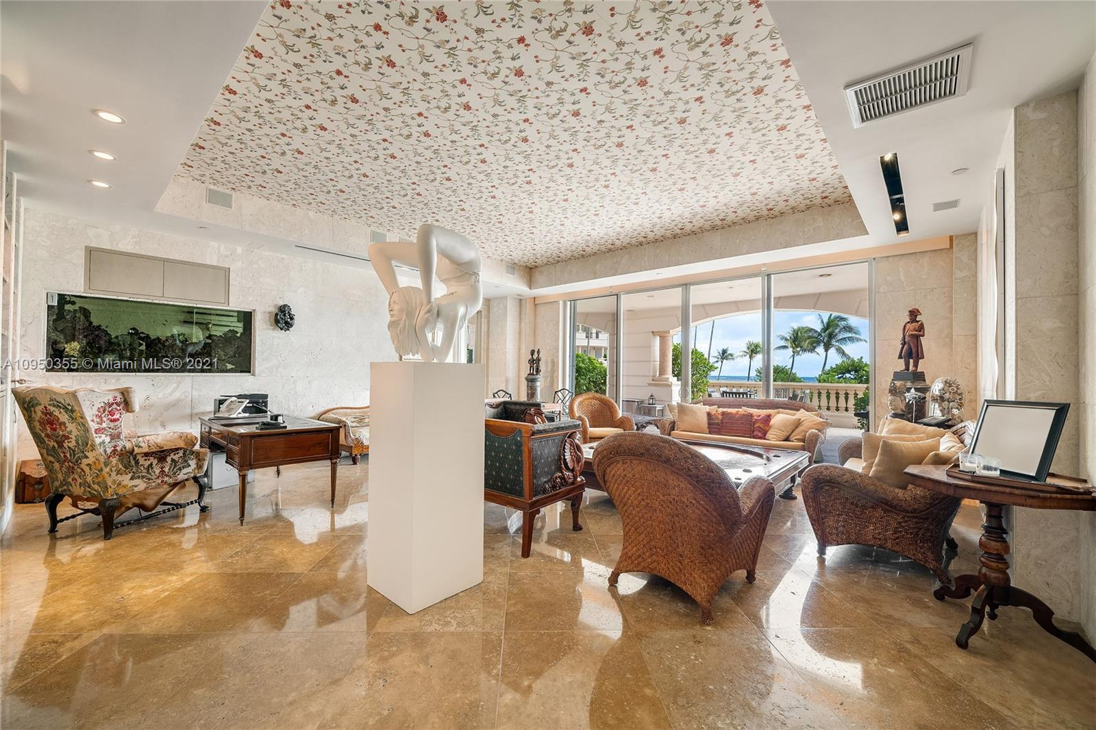 This one-of-a-kind 5BR/6+2BA ground floor townhouse is truly like no other on Fisher Island. The 2-story unit boasts 6,268 SF of luxury w/stunning custom finishes, coquina stone walls, exquisite marble floors & expansive ground floor terrace plus 2nd floor terrace both w/mesmerizing views of the beach & ocean. The principal suite is spacious, beautiful principal spa bathroom, adjacent family room, den/office & 2 additional bedrooms each w/full baths. The second level is accesses by an elegant stone/glass staircase & features a spacious formal living & dining rooms w/ terrace access & direct ocean views, chef's kitchen w/top-of-the-line appliances, staff quarters & large guest suite. Your private beach awaits outside your home. 5-Star Fisher Island amenities complete this amazing offering.