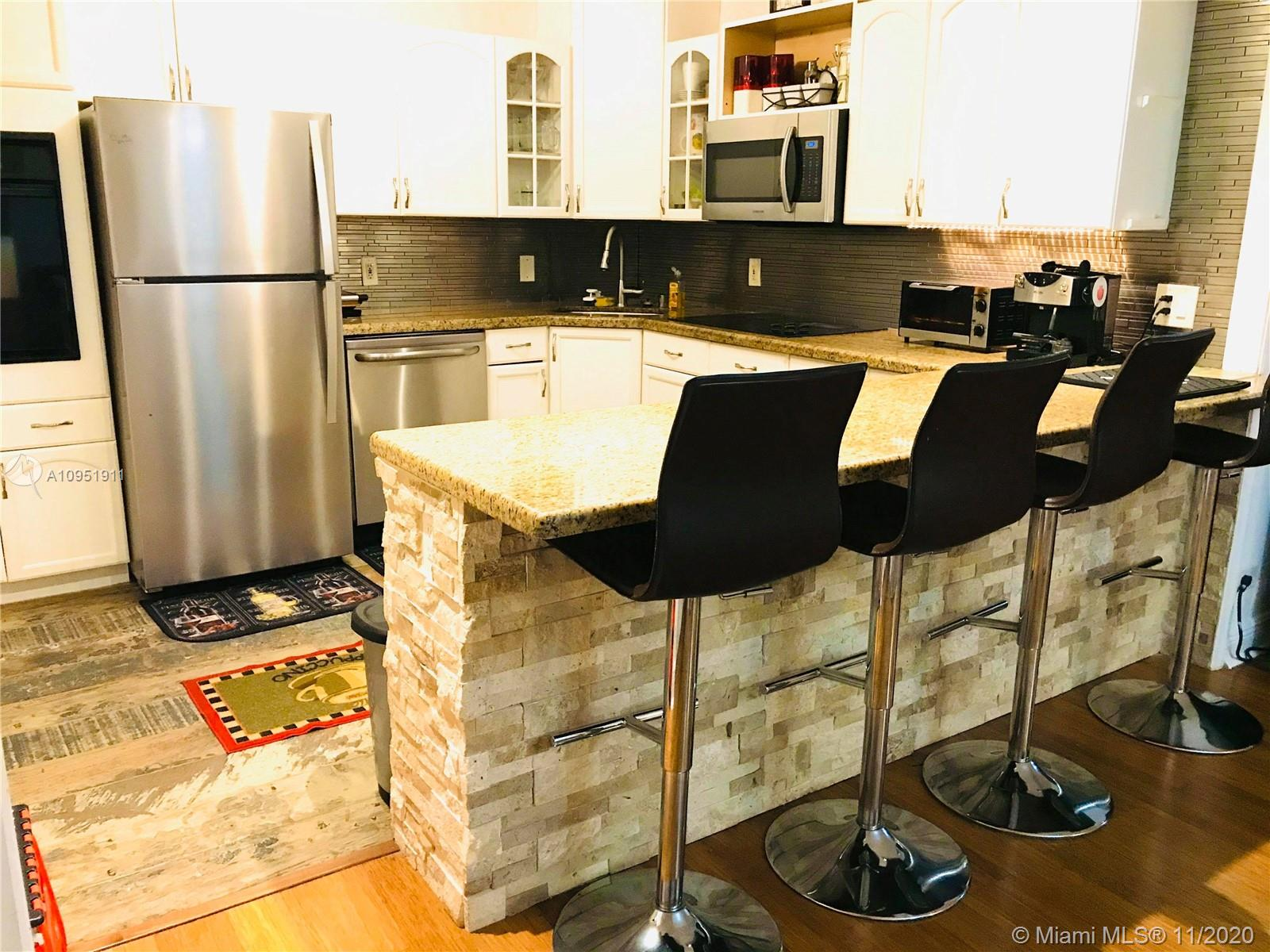 Beautiful updated 2/2 in Longwood Towers on gorgeous Bay Harbor Islands. This end unit has a private balcony with tranquil partial water view. Lots of light, hardwood floors, granite kitchen countertops and stainless appliances. Split bedroom plan with large closets. Master bedroom has three (3) closets and private bathroom with white porcelain floor. Separate closet in hall for a/c air handler, BONUS additional storage space on first floor, private parking spot, and free visitor's parking! Short stroll to top A+ school Ruth Broad K-8, Bal Harbor Shops, wonderful dining, lovely parks, and phenomenal beaches. Low maintenance fee includes water, garbage and pool. Rentals allowed after first 2 years.