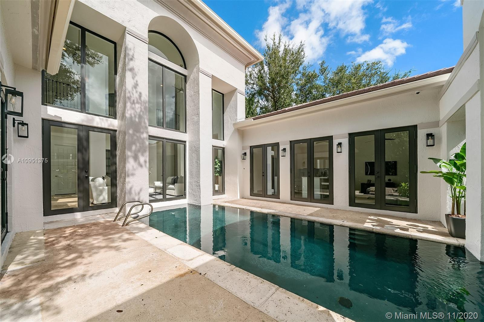 This sophisticated and elegant retreat with 4,319 Sq.Ft. was designed to offer comfort and absolute tranquility. The soaring front entry leads to an open floor plan that blends indoor and outdoor living. The light-filled living room with floor-to-ceiling windows offers views of a lap pool and courtyard. Situated beside the dining room is a modern kitchen with high-end appliances, white quartz island, and a breakfast bar with seating that opens to a family room,  ideal for entertaining.  Also on the first level is the main suite, with a stunning spa-like bathroom, walk-in closet, and glass doors that open to a pool and patio area with comfortable seating. Upstairs are 2 additional bedrooms, with en-suite bathrooms. The spacious driveway and a 2-car garage complement this extraordinary home.
