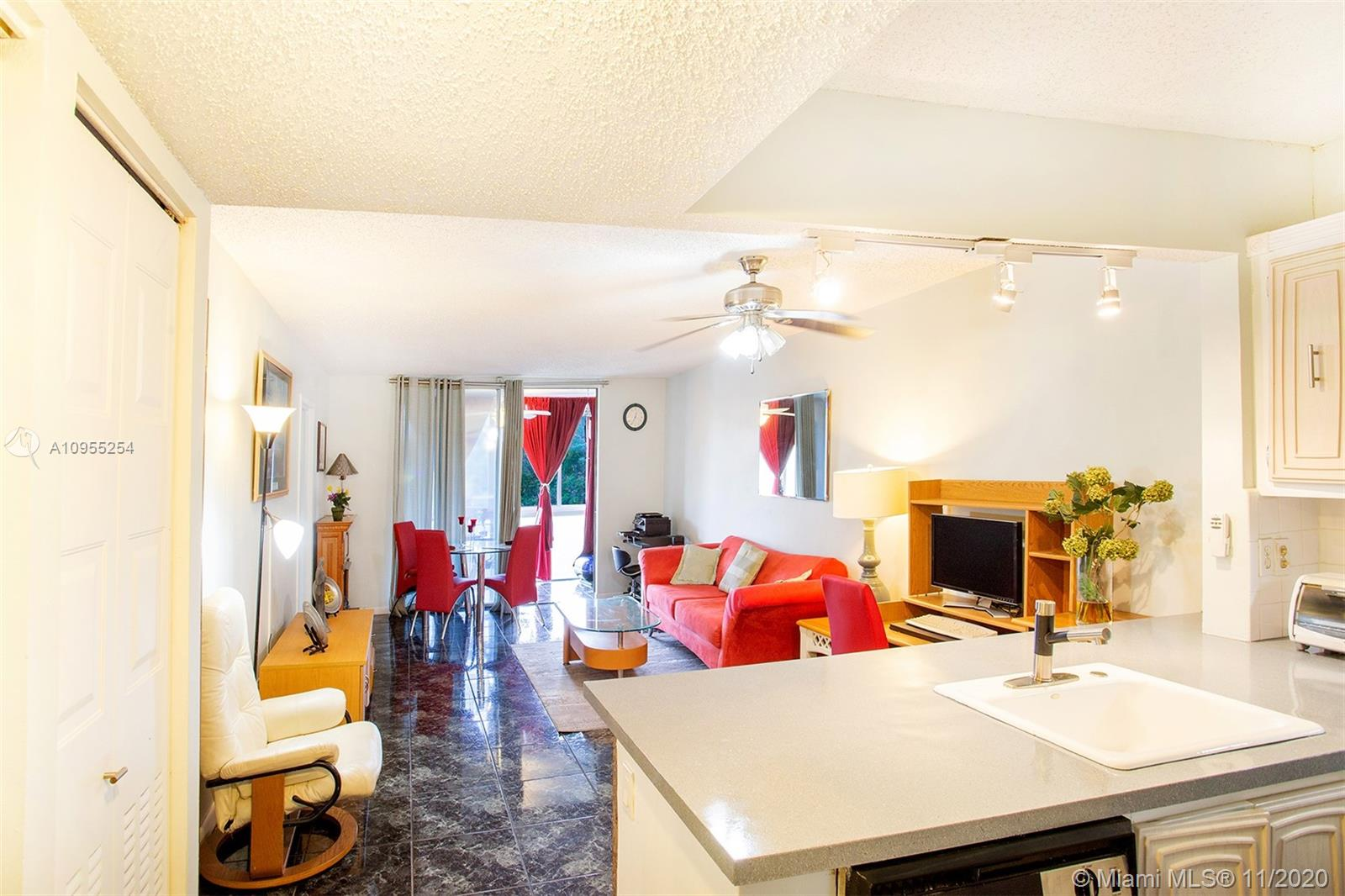 Amazing Large corner 2 beds/ 2 baths top floor unit + FLA Room. Well maintained, open concept kitchen. Large Master bedroom with walk-in closet and bathroom. New impact glass windows overlooking clubhouse and pool. Active 55+ gated community. Partial lake, pool, and sunset views.**PERFECT LOCATION (15-20 mins) to the beach and FLL airport and surrounded by shopping centers and close to I-95. No pets allowed. Low maintenance including cable with an extensive menu. Plenty of amenities: park-like walking areas, large swimming pool, laundry room on each floor, brand new clubhouse, sauna, fitness center, BBQ/Picnic area, and community activities. *** Absolute MUST SEE!*** READY TO MOVE IN! *** PERFECT FOR RELOCATION OR INVESTMENT.*** 24-hour live gate security.