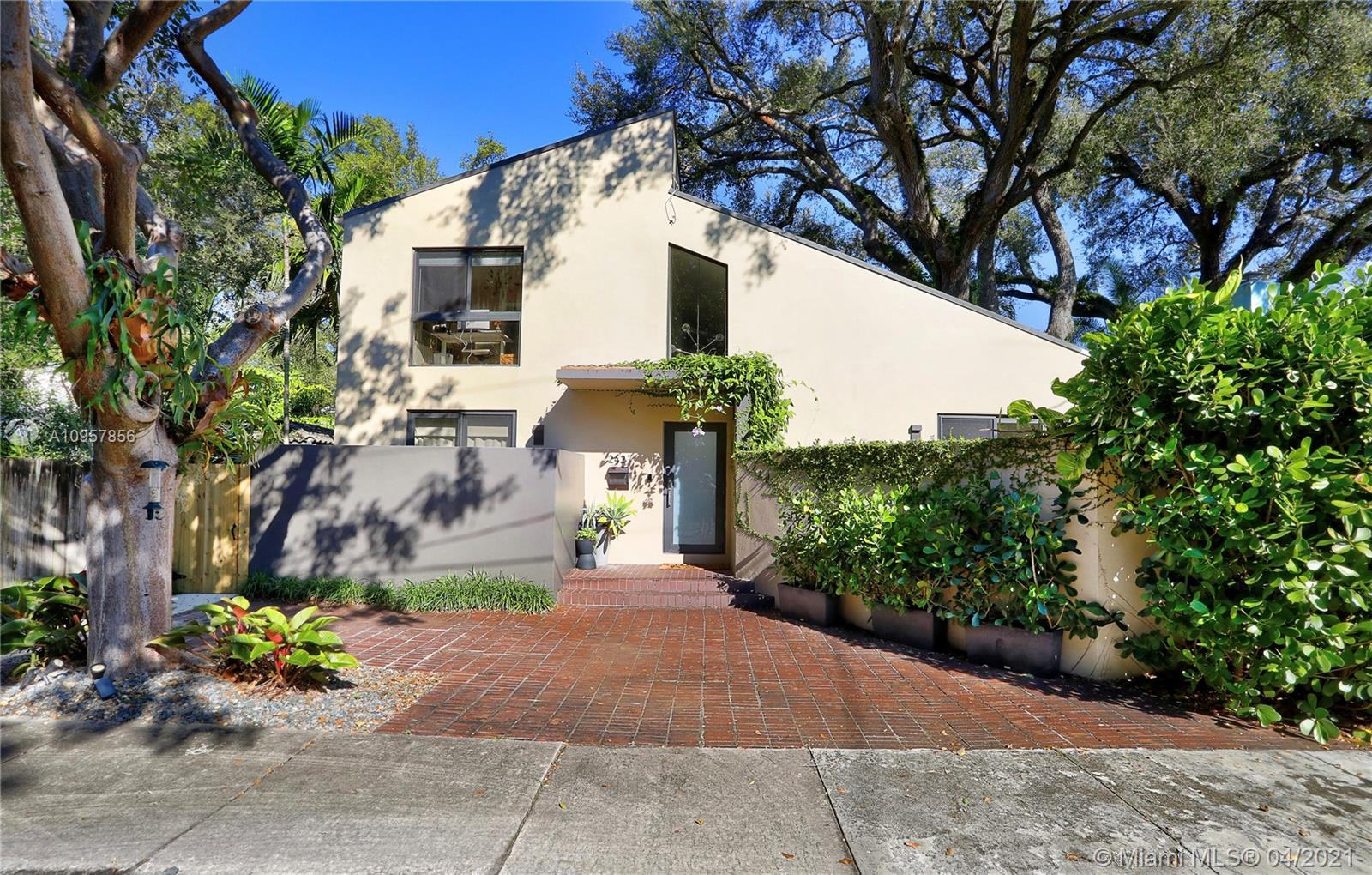 Fully updated contemporary Coconut Grove 3/2.5 bath home on quite 'no through traffic' St, PLUS A BONUS LOFT SPACE. This North Grove home is built around a 100+year old Oak tree & features volume ceilings, gorgeous wood floors in bedrooms and porcelain tiled floors in living area, w/high impact windows & doors throughout! Bedroom with fully remodeled bathroom located on the 1st floor. Upstairs; 2 bedrooms w/remodeled Jack & Jill bathroom. Loft currently being used as a 4th bedroom, but is ideal as a kids playroom or office. Separate laundry room off  kitchen w/storage space. There are 3 patio spaces which include a Jacuzzi hot tub and pergola for entertaining. The pergola has a custom dining table which comfortably seats 12 people. Flood zone 'X'. Come and see this pristine turn key home!