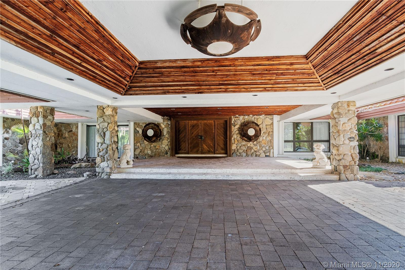 """This iconic Weston home affectionately nicknamed the """"House with The Horses"""" could be yours. This mansion sits on a large estate with a vast lake frontage and luscious vegetation. The centerpiece of the living room is a massive stone fireplace that culminates into a cowhide-covered ceiling. You truly feel like you are standing in an African Safari Lodge. The backyard has a pool, a large chess set, and a pair of gazebos. One gazebo has 2 bedrooms of its own, and a full bathroom, while the second gazebo has 1 bedroom, a full bathroom, and a kitchen. Unique to this Weston mansion is a walk-in safe that can be utilized as a safe room. The master bedroom's walk-in closets are lined with Cedarwood. The driveway leads you to the magnificent wooden entrance of the mansion or to a 3-car garage."""