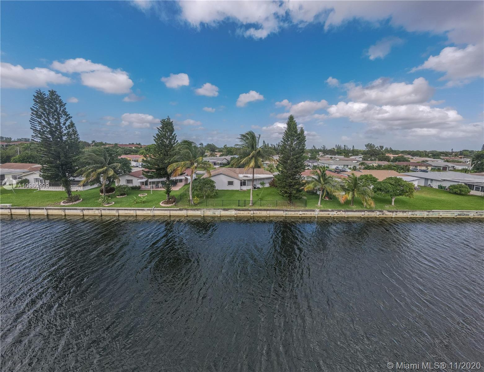 Come enjoy the views of this fully updated & immaculate waterfront home in this ALL AGES community.  3 bedrooms, 2 baths w/ a larger lot than the average home in Westwood Community. Spacious 2 car garage. Walk into your open floor plan w/ plenty of room for entertaining. Tile & laminate throughout. Updated kitchen. Stainless Steel appliances. Master bedroom has updated walk-in closet w/ built ins. Master bath w/ dual sinks & a walk-in shower. Plenty of windows & lighting. Hurricane Shutters throughout the entire home. Enclosed patio perfect for hosting. Large Backyard overlooks an amazing lake, great for outdoor pets & can fit a pool. Lots of privacy w/ no neighbors behind. NEW A/C, 2019. NEW Water Heater, 2020. Extremely low HOA includes common areas, landscaping & community pool.