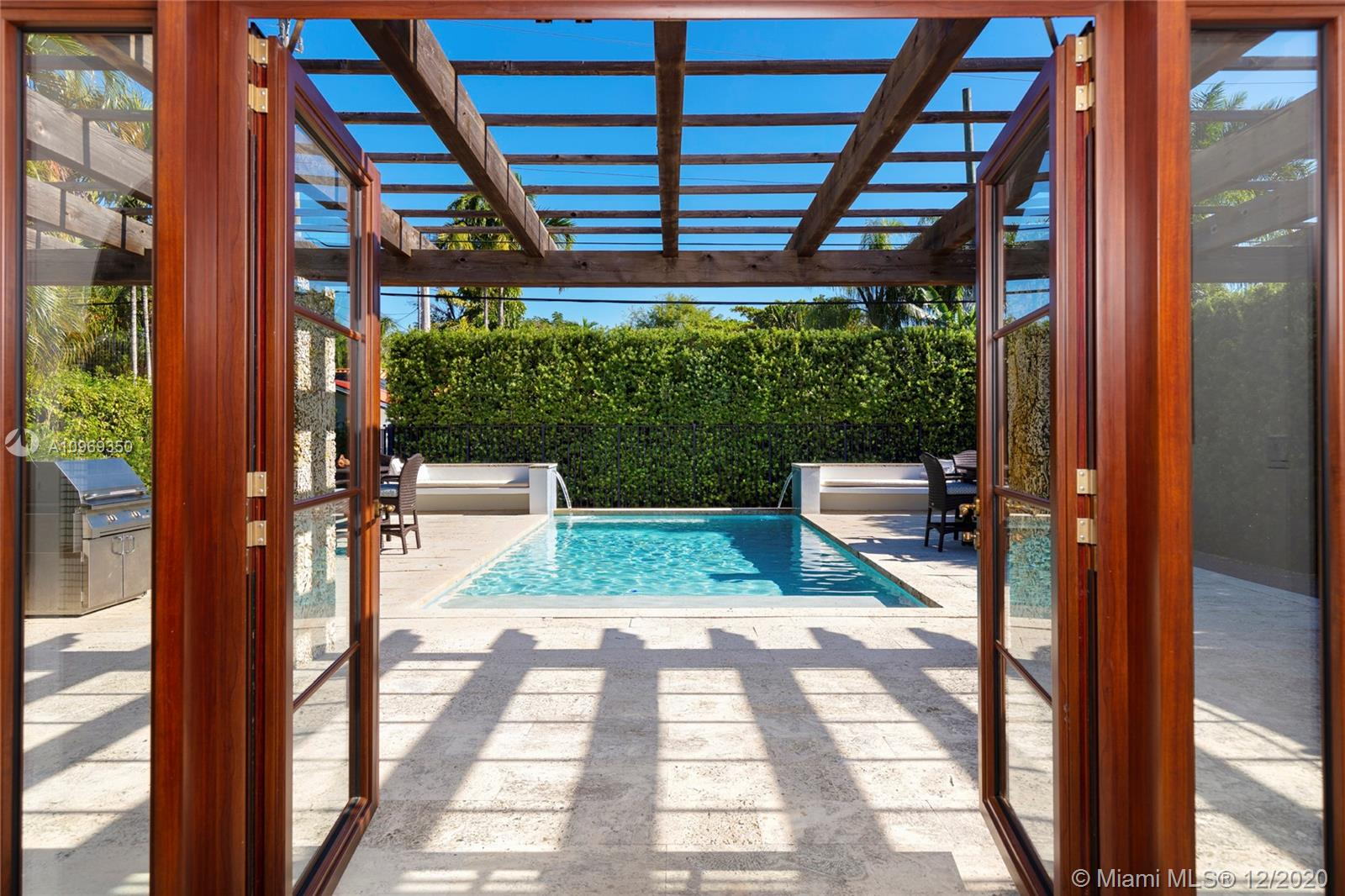 Located on an idyllic neighborhood street in the North Grove, just steps from Biscayne Bay and an incredible lifestyle. This warm and inviting home features marble floors, custom kitchen with high-end appliances, new roof, plumbing, and electrical. Through the Italian impact doors, you'll see the crown jewel of the home – an inspired, Portuondo Perotti pool terrace with pergola, coral rock columns, outdoor shower, and waterfall.  The backyard oasis truly feels like its own vacation getaway! Behind the lush privacy hedge discover a secret garden of fruit trees and space to create whatever brings you joy. Immaculate and worry-free, this home is the one you have been waiting for!