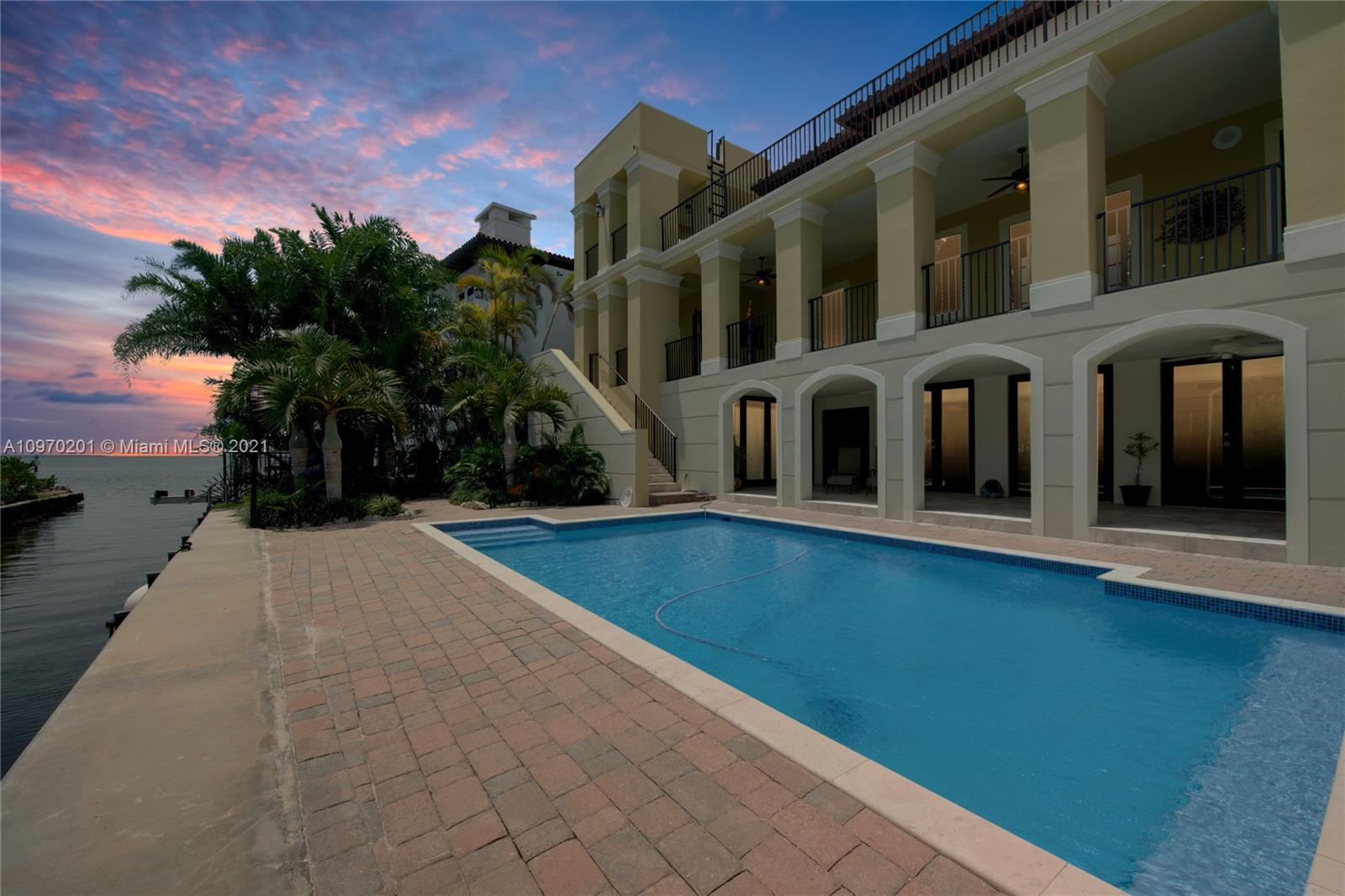 Stunning and impressive one of a kind property in the heart of Coconut Grove.  Nestled at the private end of Poinciana Avenue, within the guard-gated prestigious Four Way Lodge Estates. Breathtaking views of downtown Miami and Biscayne Bay. Spectacular oversized terraces run along all three levels and can be accessed from almost every room. Property is complete with gourmet chef's kitchen/butler's pantry, elevator, multiple living areas, fireplace, three car garage, impact windows, heated salt water system pool, boat davits, and so much more. Impressive master suite with his/hers bathrooms and closets. All bedrooms are en suite. Over 1000 square feet of enclosed a/c bonus recreation/reception space. The perfect home for entertaining. One house from the bay. Must see to appreciate.