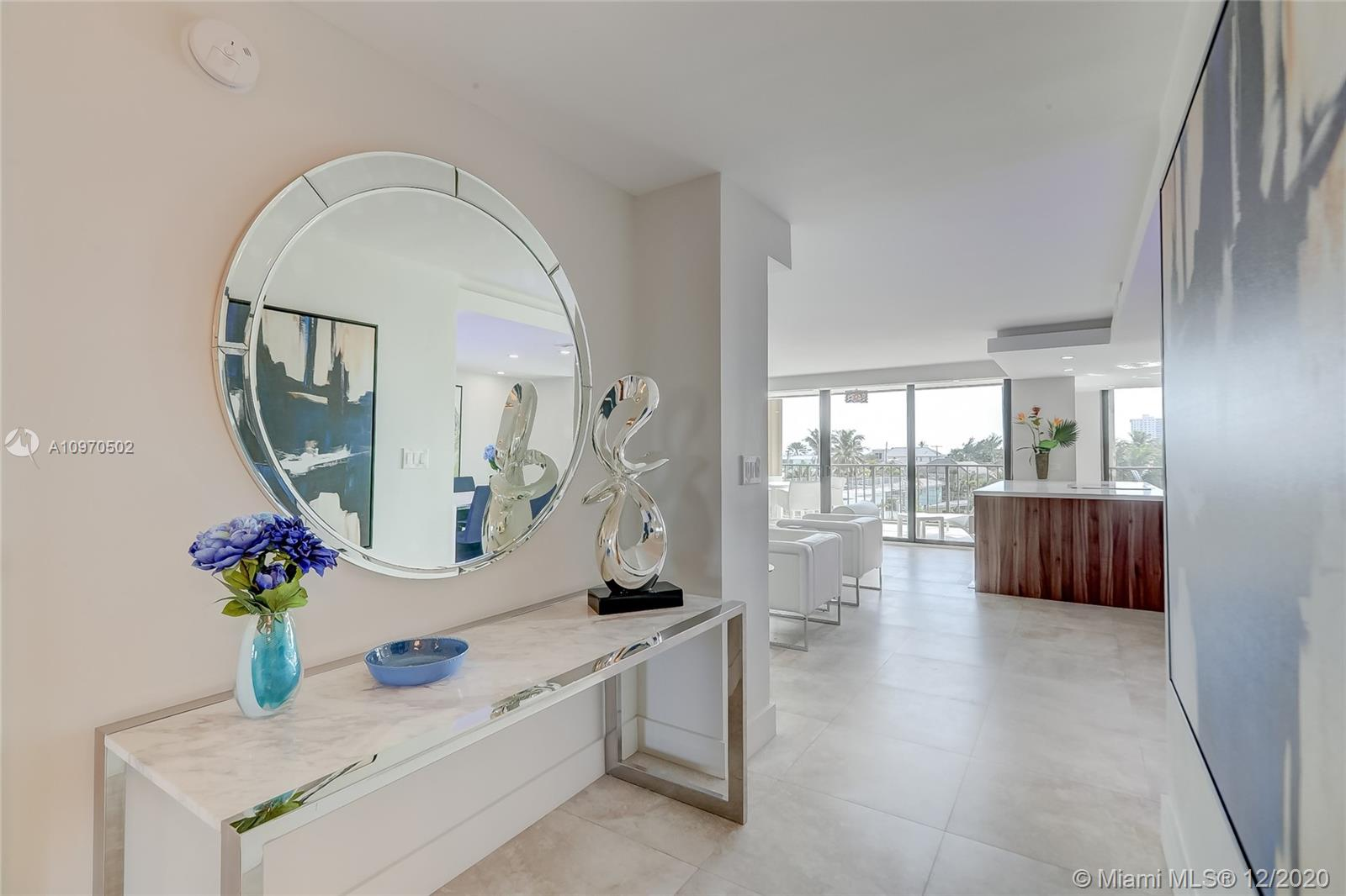 Nothing has been overlooking in this remodeled 1500sf 2 bed/ 2 bath condo along Ft. Lauderdale Beach. From the second you walk into this condo off your elevator foyer, you can see the attention to detail. This professionally decorated condo has an open floorplan with large ceramic tile throughout. Modern kitchen with quartz countertops, under cabinet lighting and all the top stainless steel appliances. Dropped ceilings with recessed lighting. Custom glass wine shelving. Both bathrooms have custom fixtures and walk-in showers with frameless glass doors.  Large balcony with ocean views. Laundry room w/ storage. Impact glass windows and sliding doors. Gated community with doorman. Beach pavilion offers pool, gym, bbq and more.