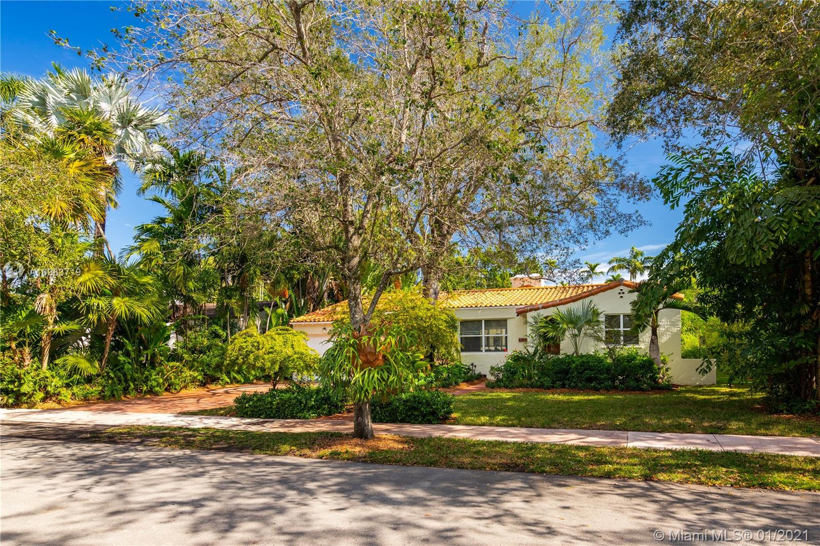 This beautiful Coral Gables home is a real find. Located on a quiet, low traffic street complete with sidewalks and quaint streetlamps, this home has been lovingly updated and expanded over the years. Luscious landscaping, replete with a butterfly garden and a large 11,100 sf lot, provides much breathing room and outdoor spaces to play and entertain. The split floorplan and the generous living spaces check more essential boxes off a buyer's wish list. Who would not want to cook in this fabulous kitchen? The master suite includes an updated spacious bath, large walk-in closet, and a bay window begging for you to curl up with a book while overlooking the pool. Impact doors and windows allow lots of natural light.  Major renovation was completed in 2006. A Very Special Home.