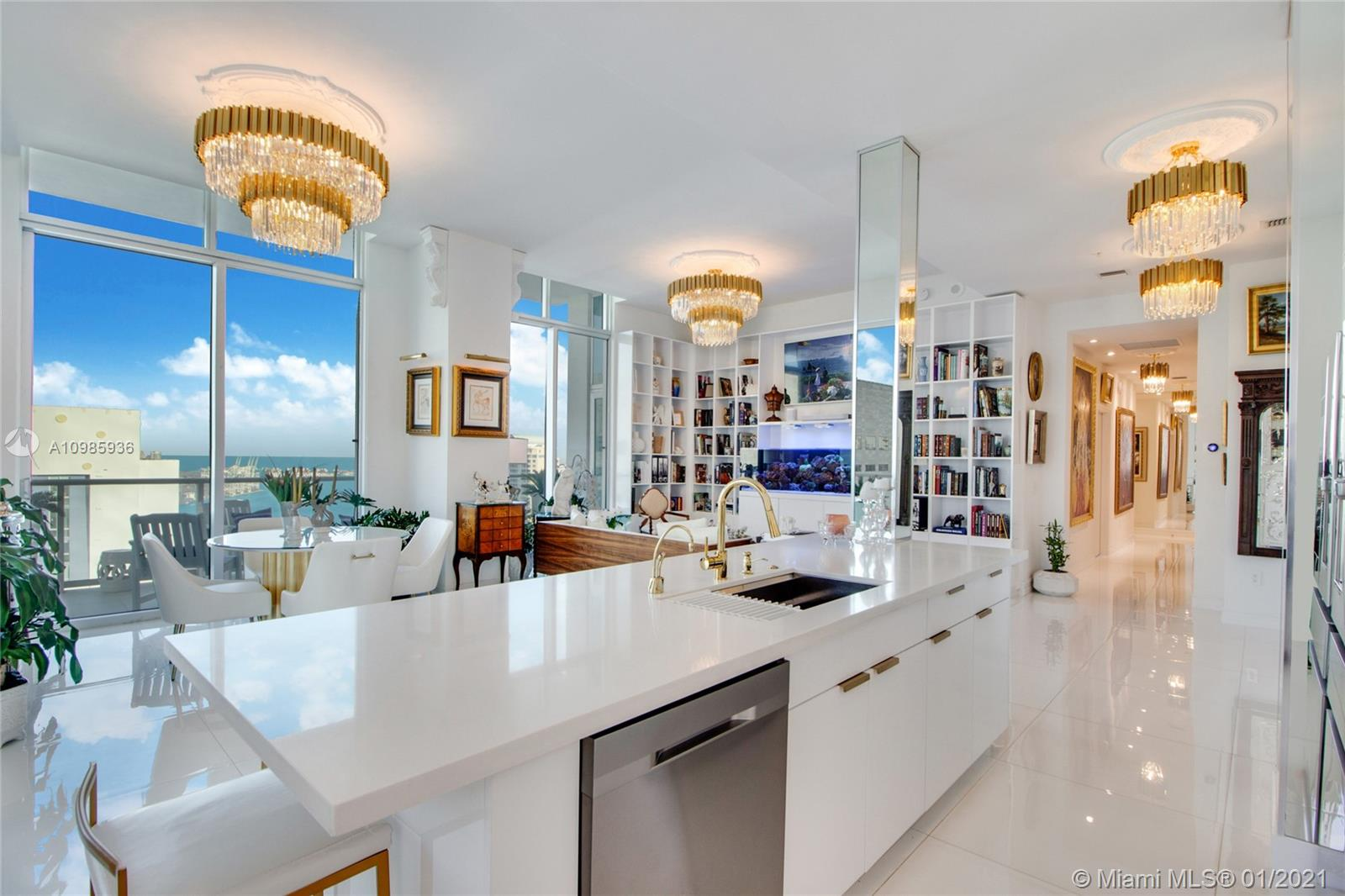 Welcome to 4006 at Met 1, where beauty and luxury meet comfort and leisure. Completely redesigned in 2020 in palatial white and gold, this Downtown Miami penthouse offers a unique opportunity. Entertain effortlessly in the lounge with custom cabinetry boasting a 100+ wine bottle cellar, built-in ice maker, and a sleek dual tap draft beer refrigerator. The lounge also has direct access to the wraparound balcony. The stunning kitchen has been expanded and finished with high-end appliances. As you walk through the art-filled gallery/hallway, you'll find the impeccably designed bedrooms, each with custom walk-in closets, spa-like bathrooms, and a second balcony to enjoy privately. Very rare opportunity to own five (5) designated parking spaces in the heart of Downtown Miami.