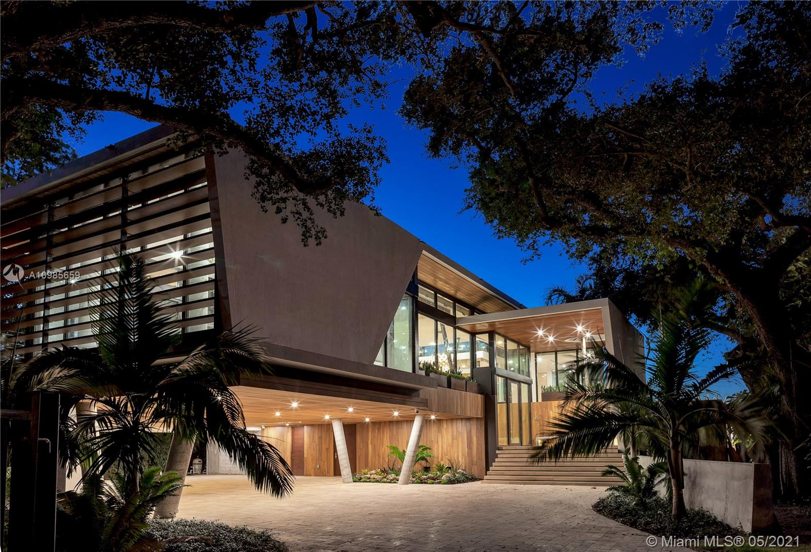 Spectacular Tropical Modern masterpiece set within a lush botanical garden behind a custom coral rock wall and gate. Designed by acclaimed architect Gabriel Lopez. The quality of finishes, fixtures and attention to detail is unsurpassed by any new construction home in the Grove. Double-height ceilings and walls of glass create a seamless blending of interior and fabulous exterior spaces. Custom Brazilian kitchen by Armazem.  Smart Home automation. 24 hour security guards. Live amongst the elite on the exclusive residences behind Viscaya Gardens.