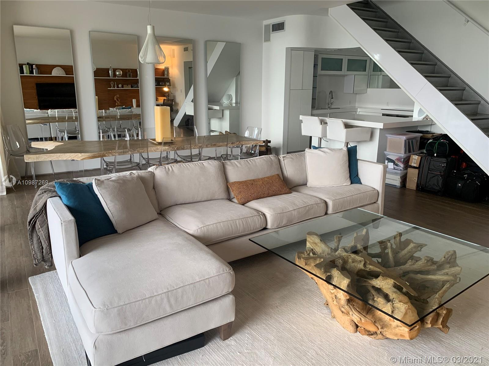 Unique two story corner unit with a million dollar view located in one of the most exclusive areas of Miami and Miami Beach! 9.5 'glass walls that open to huge balconies on each level. The master bedroom and bathroom are on the upper level. Beautiful view of downtown Miami. Unit is located on the water overlooking the beautiful dog park and intercoastal waterway. Hardwood floors downstairs and polished concrete floors upstairs in the bedroom. Lots of mirrors reflecting the incredible view. Stunning views and even the hallway of the Unit has floor to ceiling glass walls. The kitchen is modern with all white cabinets.